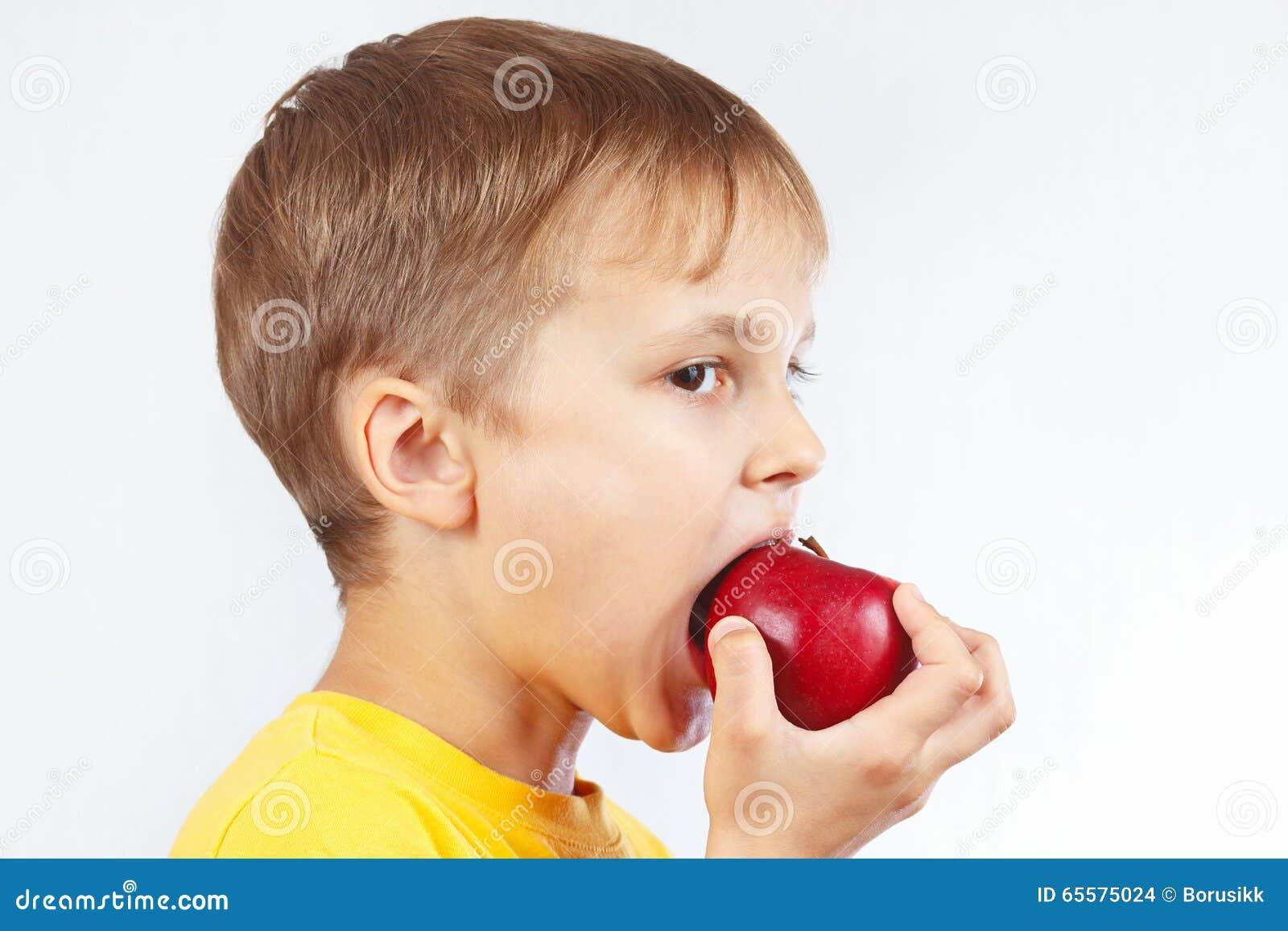 Menino novo em uma camisa amarela que come a maçã vermelha
