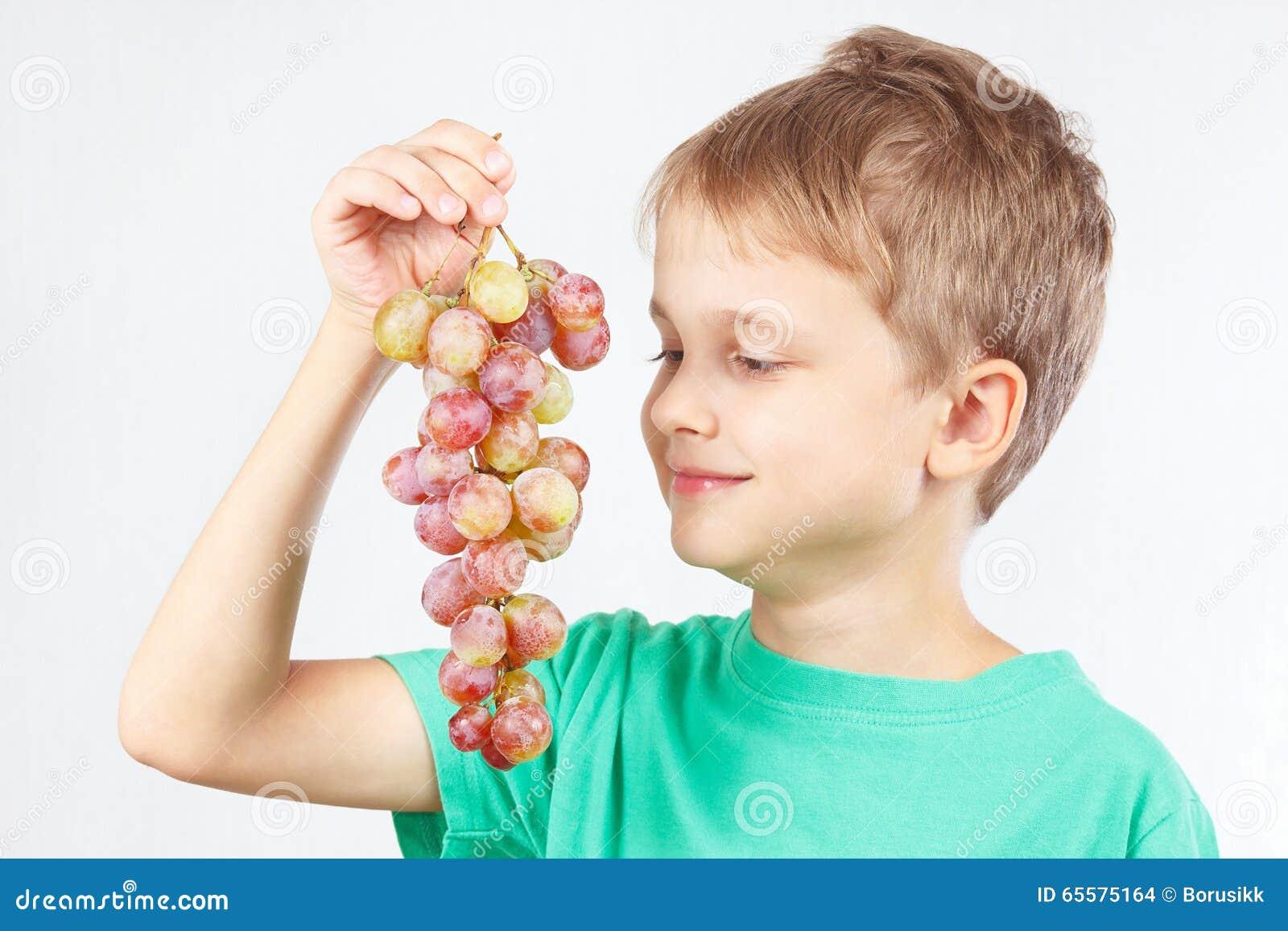 Menino novo em uma camisa verde com uva