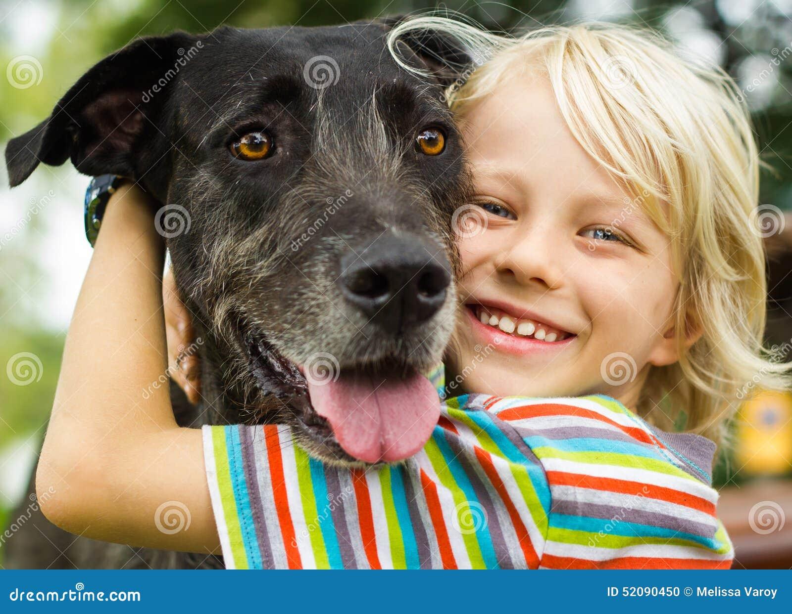 Menino novo feliz que abraça lovingly seu cão de estimação