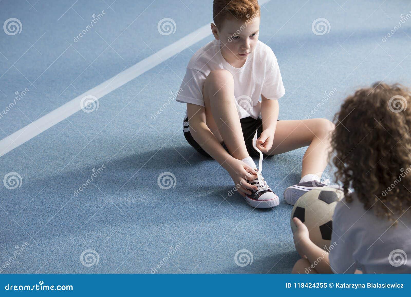 Menino novo que amarra sapatas do esporte