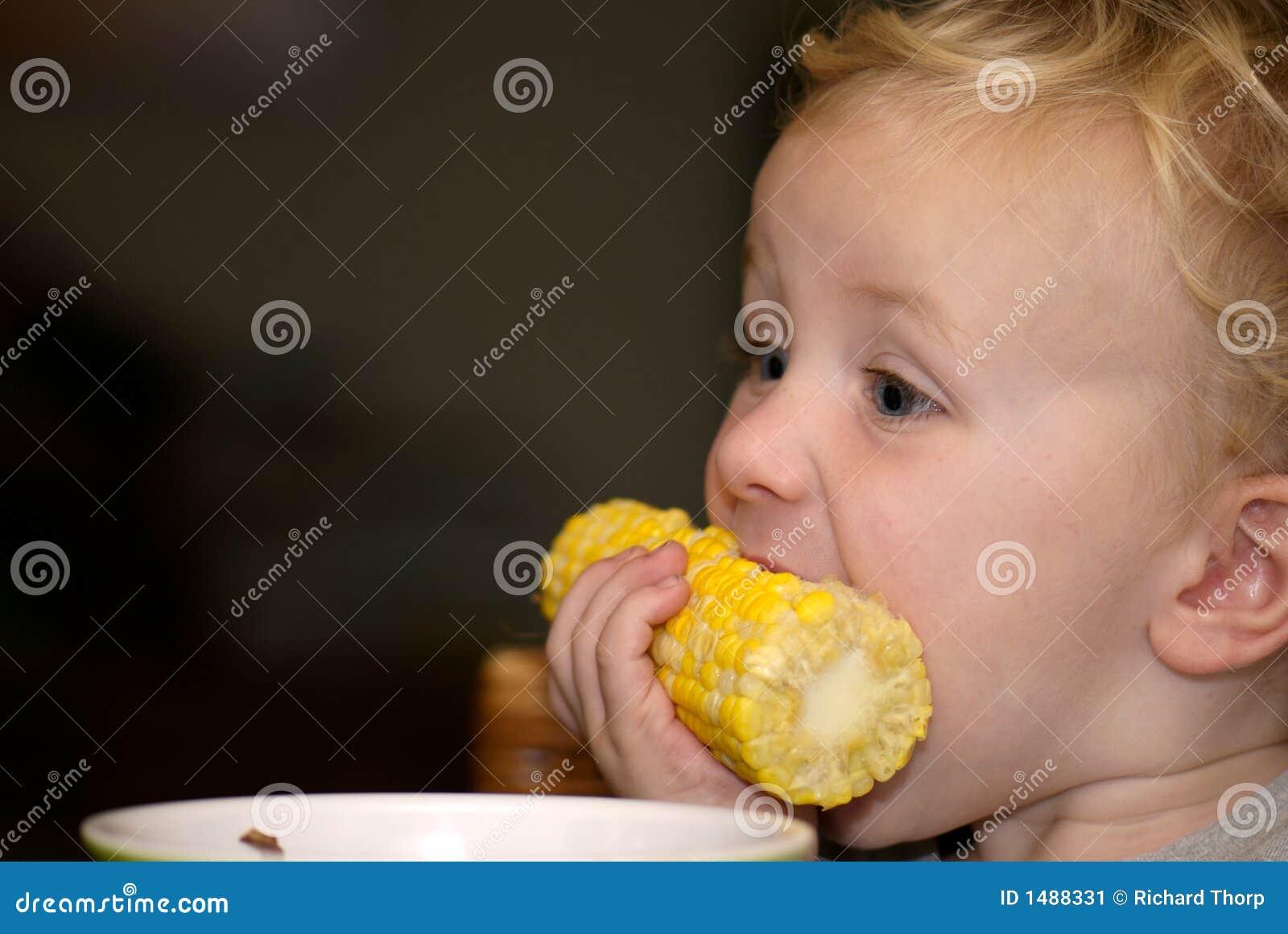 Menino novo que come a espiga de milho
