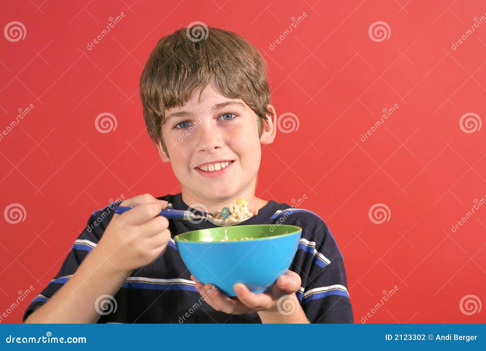 Menino novo que come o cereal