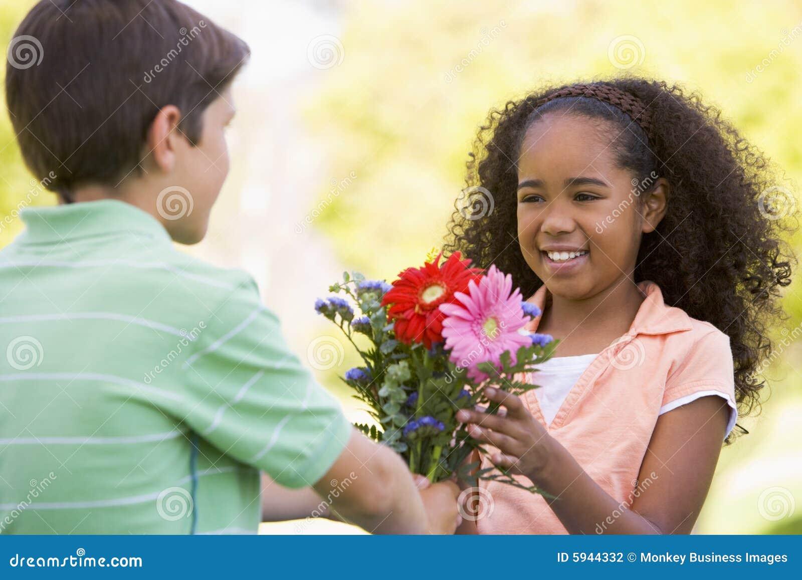 Menino novo que dá flores e sorriso da rapariga