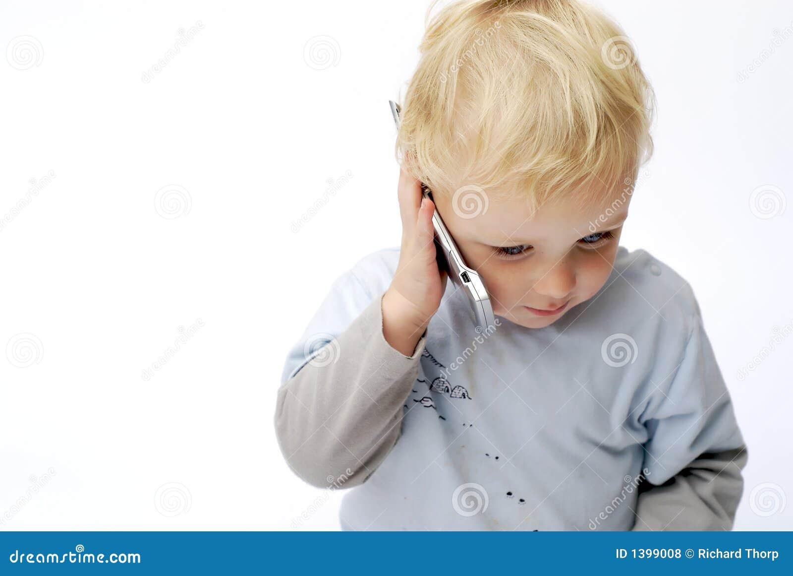 Menino novo que fala no telefone móvel