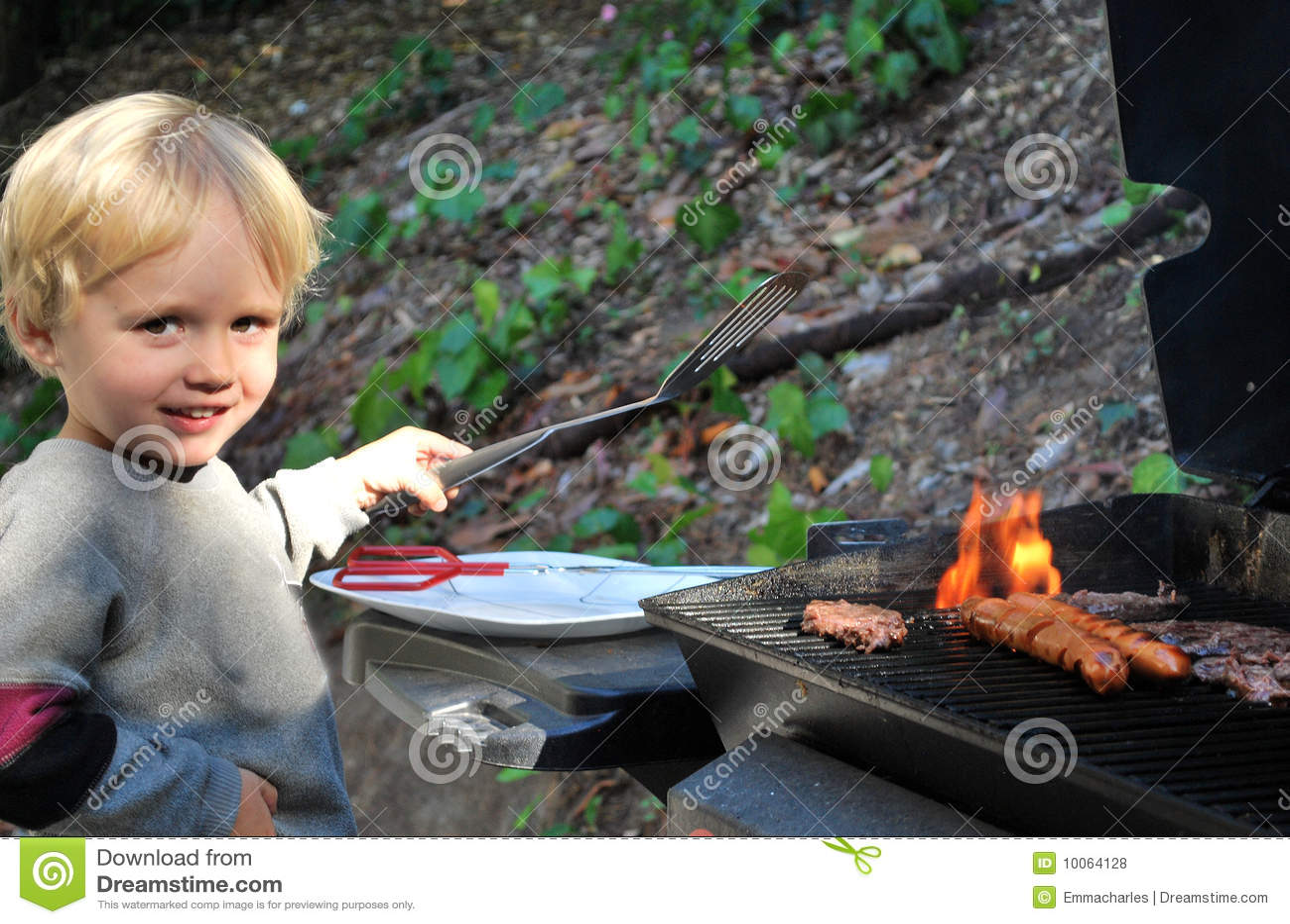 Menino novo que grelha o alimento