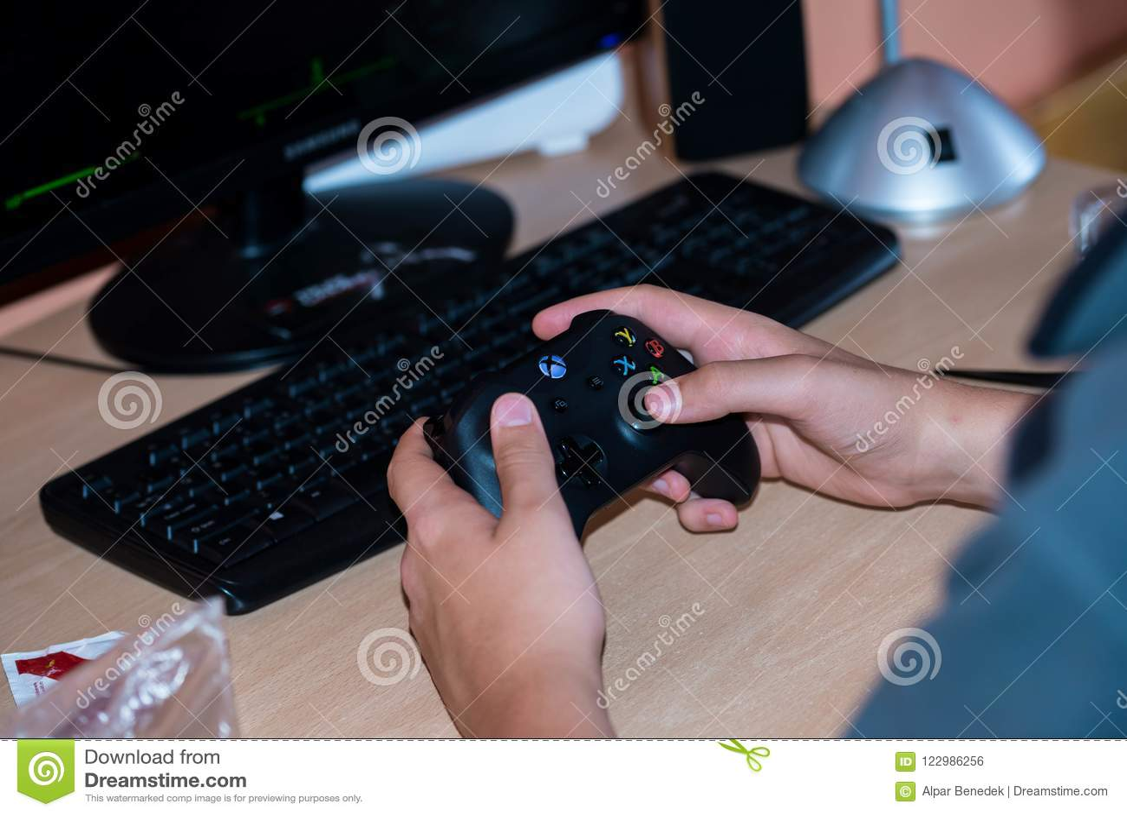 Menino novo que joga em Xbox um jogo de vídeo no computador pessoal