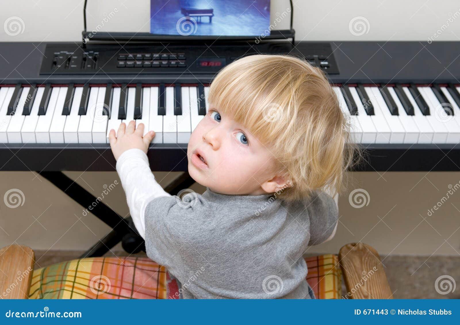 Menino novo que joga o piano ou o teclado