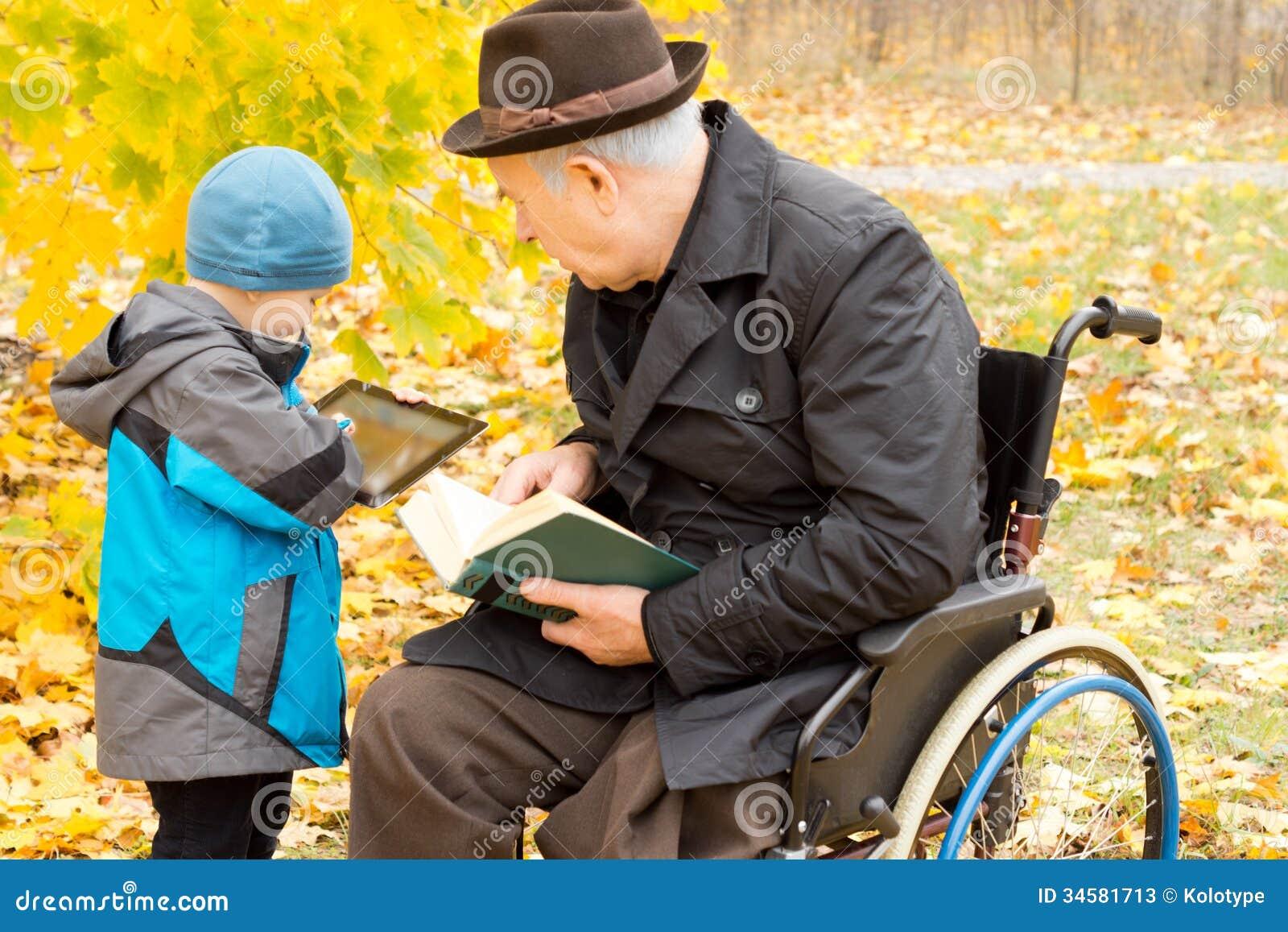 Menino novo que mostra a seu avô sua tabuleta