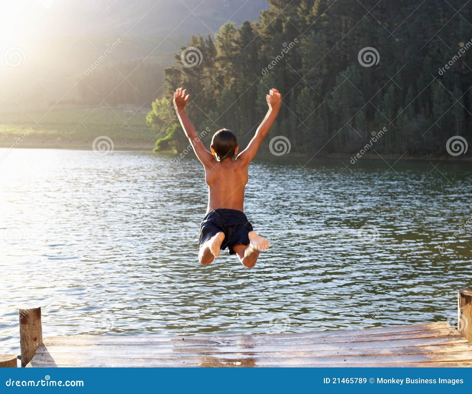 Menino novo que pula no lago
