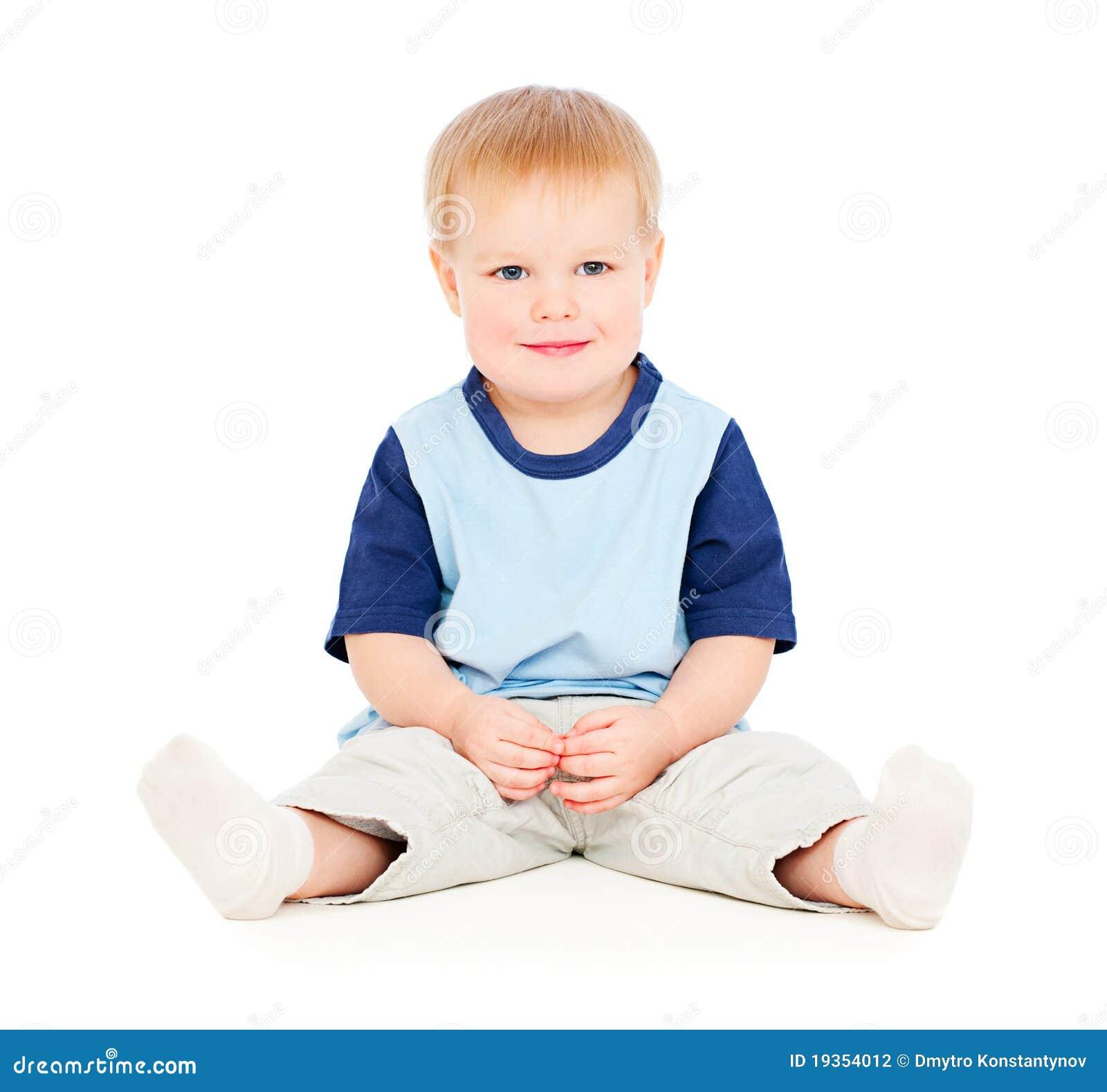 Menino novo que senta-se no assoalho