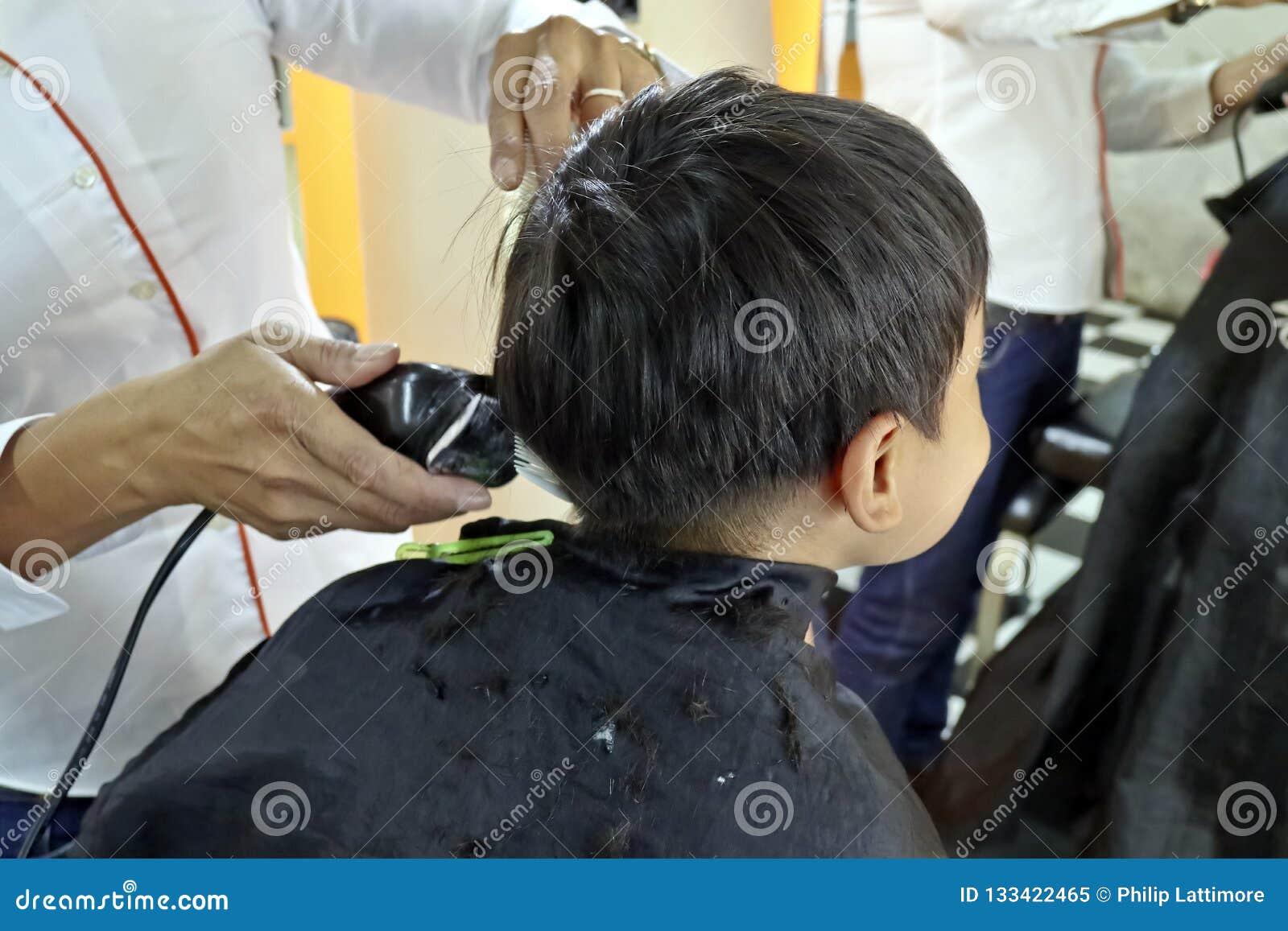 Menino novo que tem um corte de cabelo
