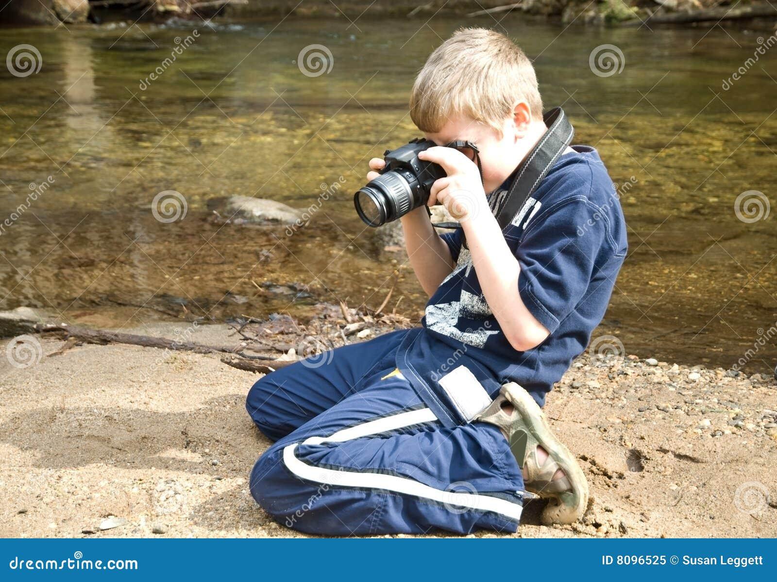 Menino novo que toma a foto/câmera
