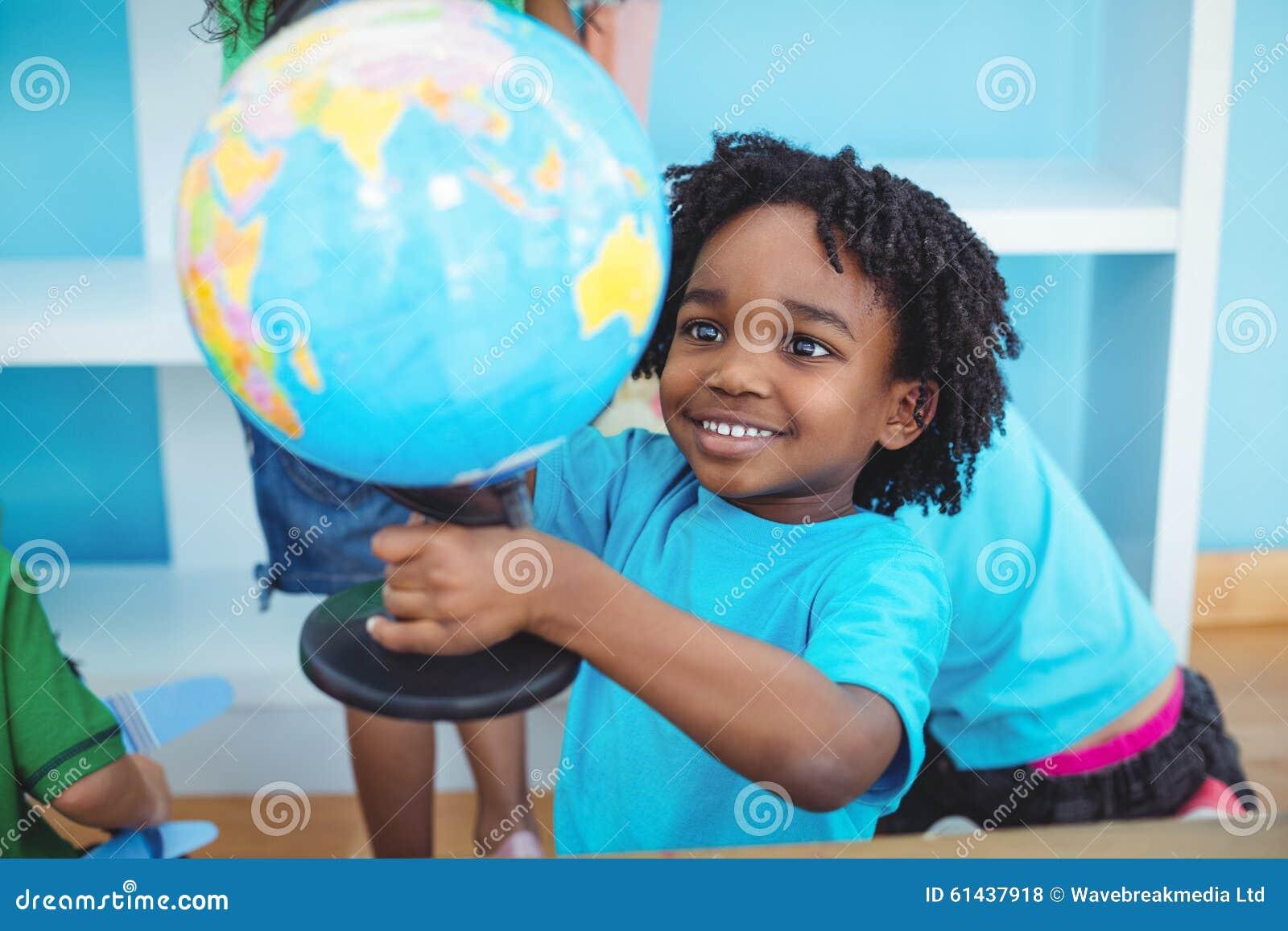 Menino pequeno que guarda um globo do mundo