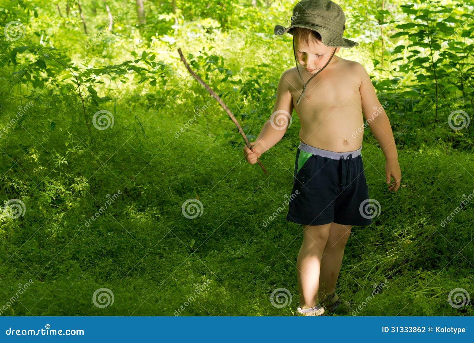 Menino pequeno que joga nas madeiras com uma vara