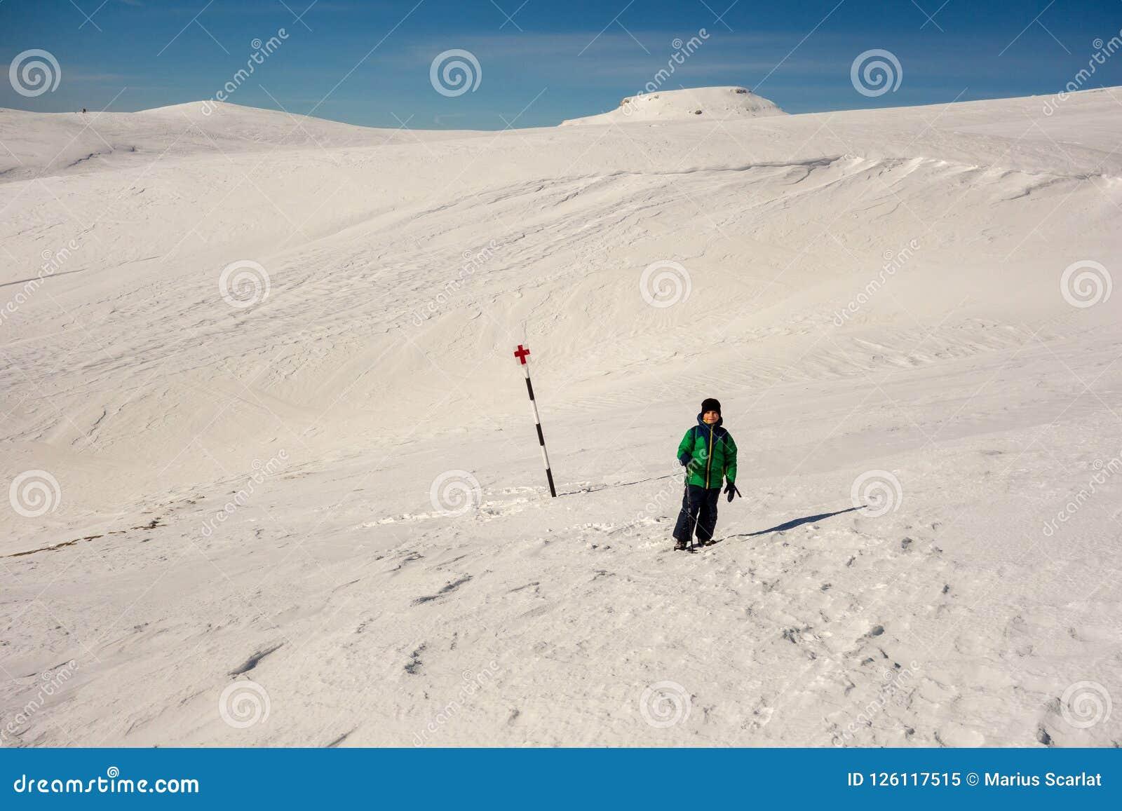 Menino que anda em um trajeto marcado na montanha