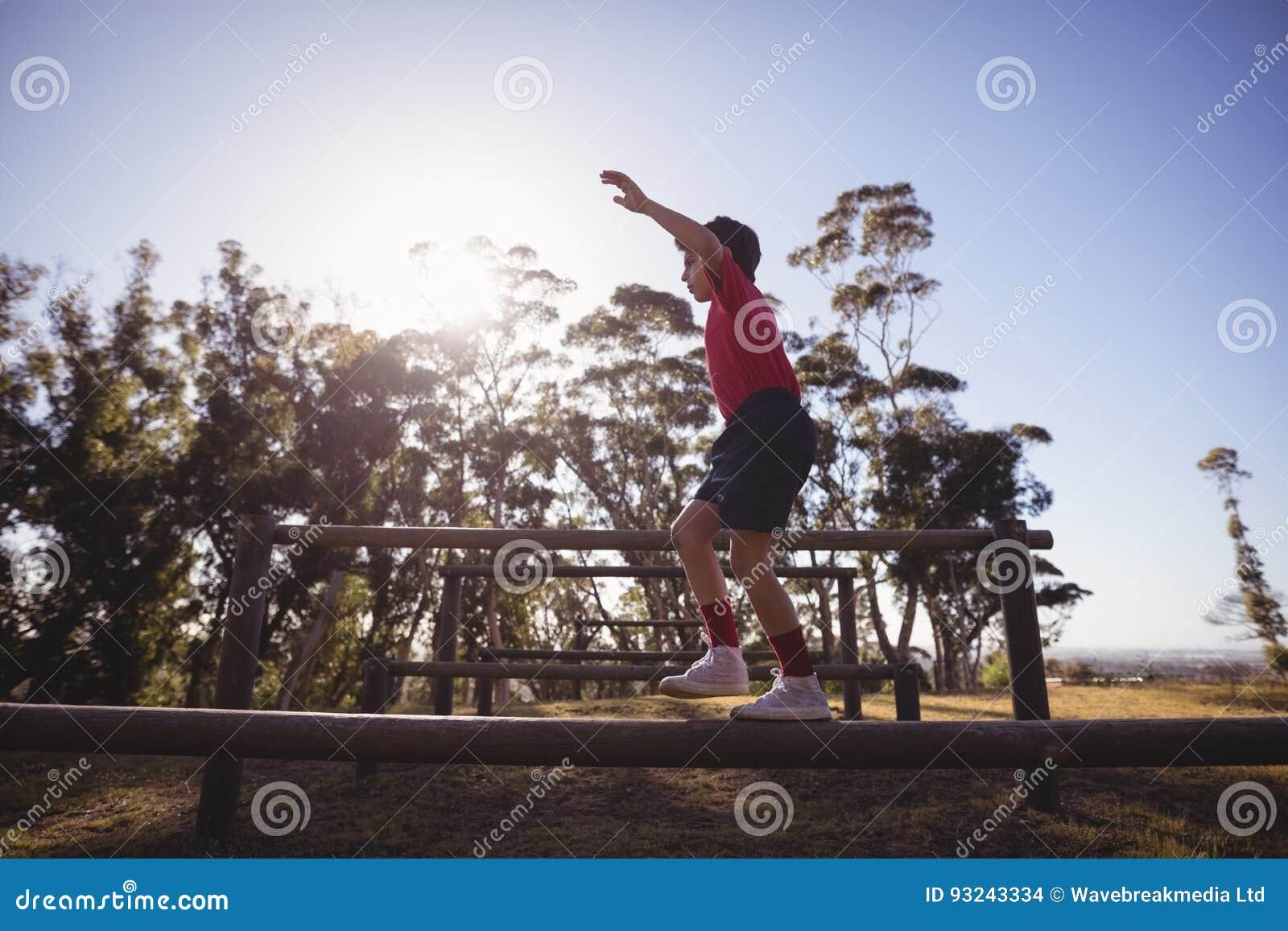 Menino que anda no obstáculo durante o curso de obstáculo
