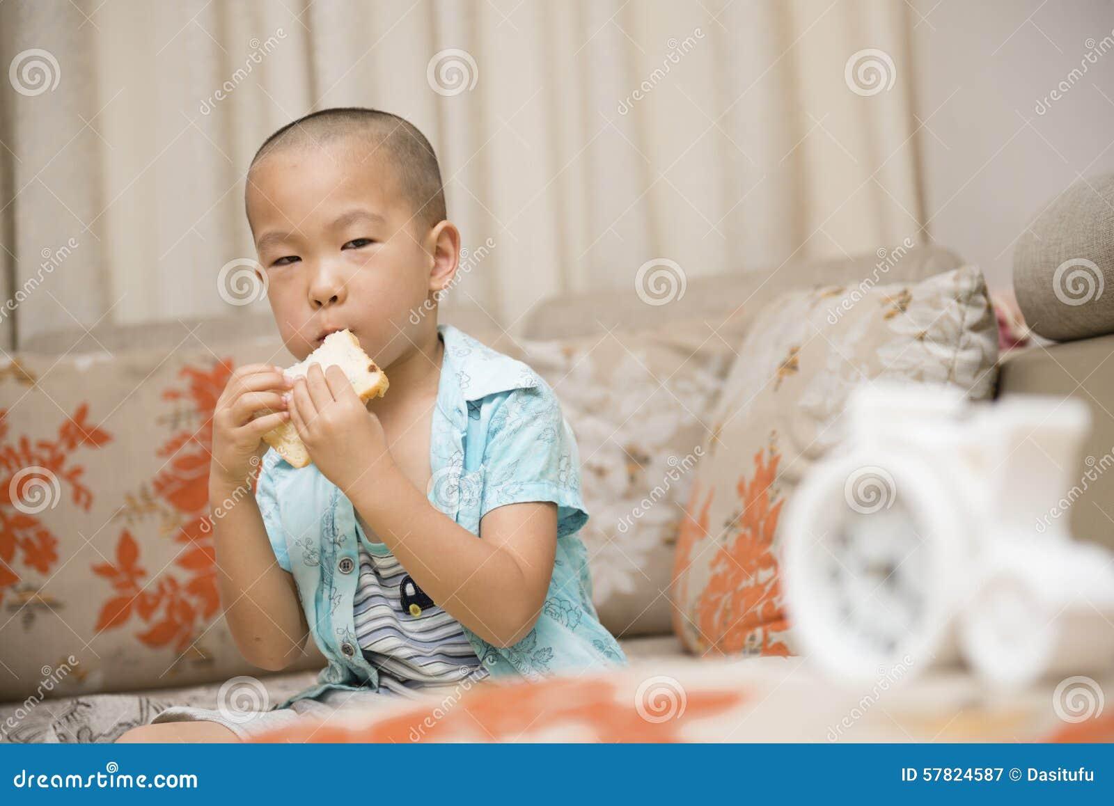 Menino que come o pão