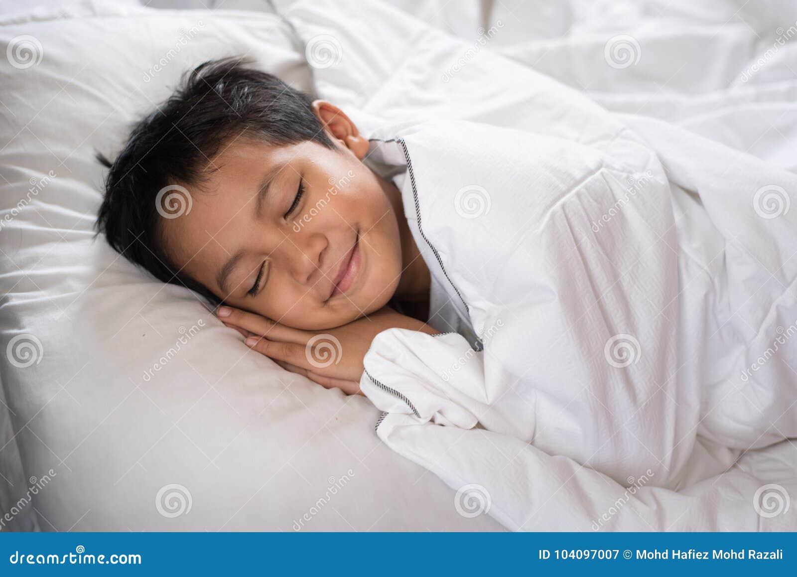 Menino que dorme com a cara do sorriso na folha e no descanso brancos de cama