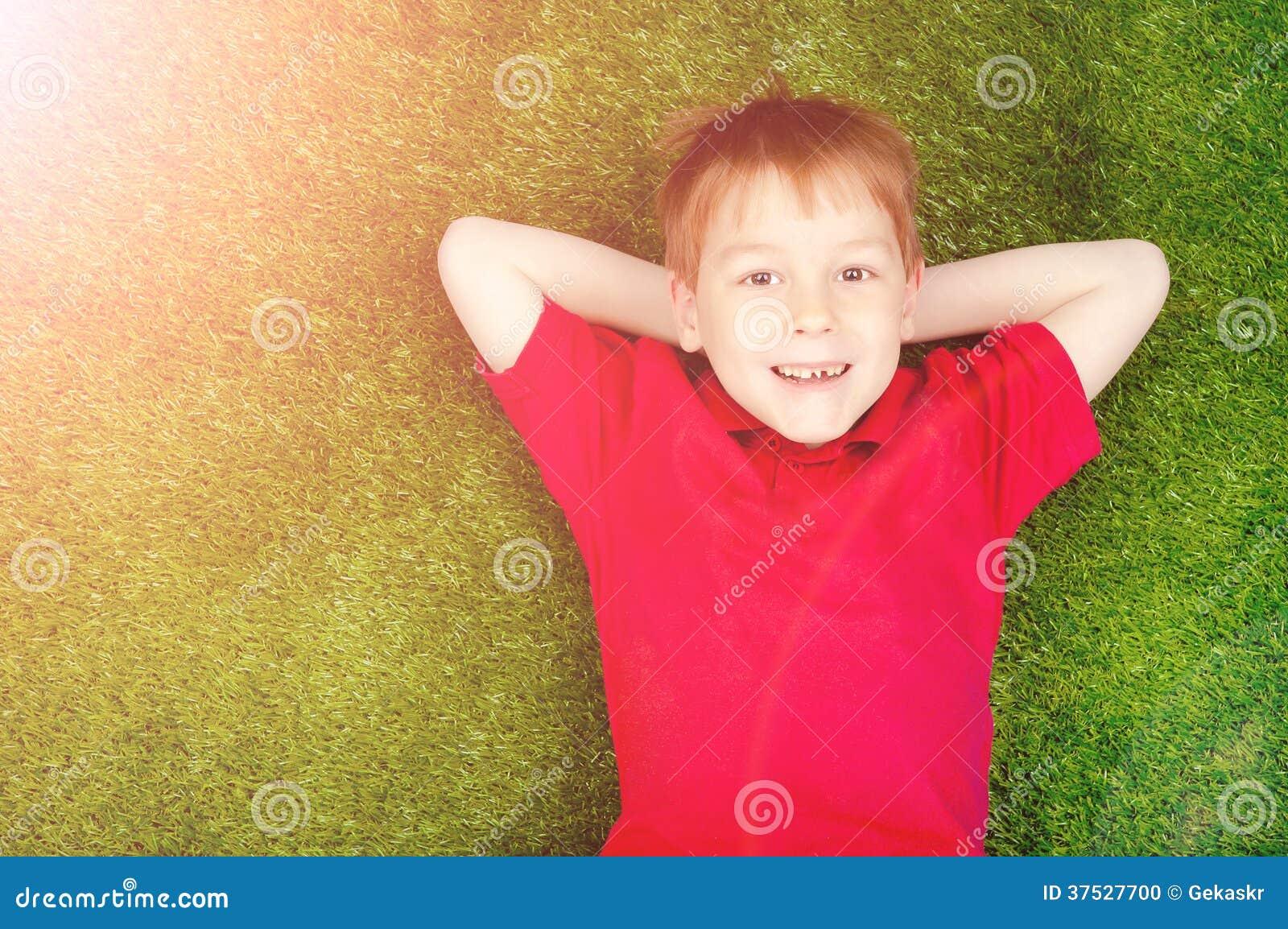 Menino que encontra-se em um gramado verde