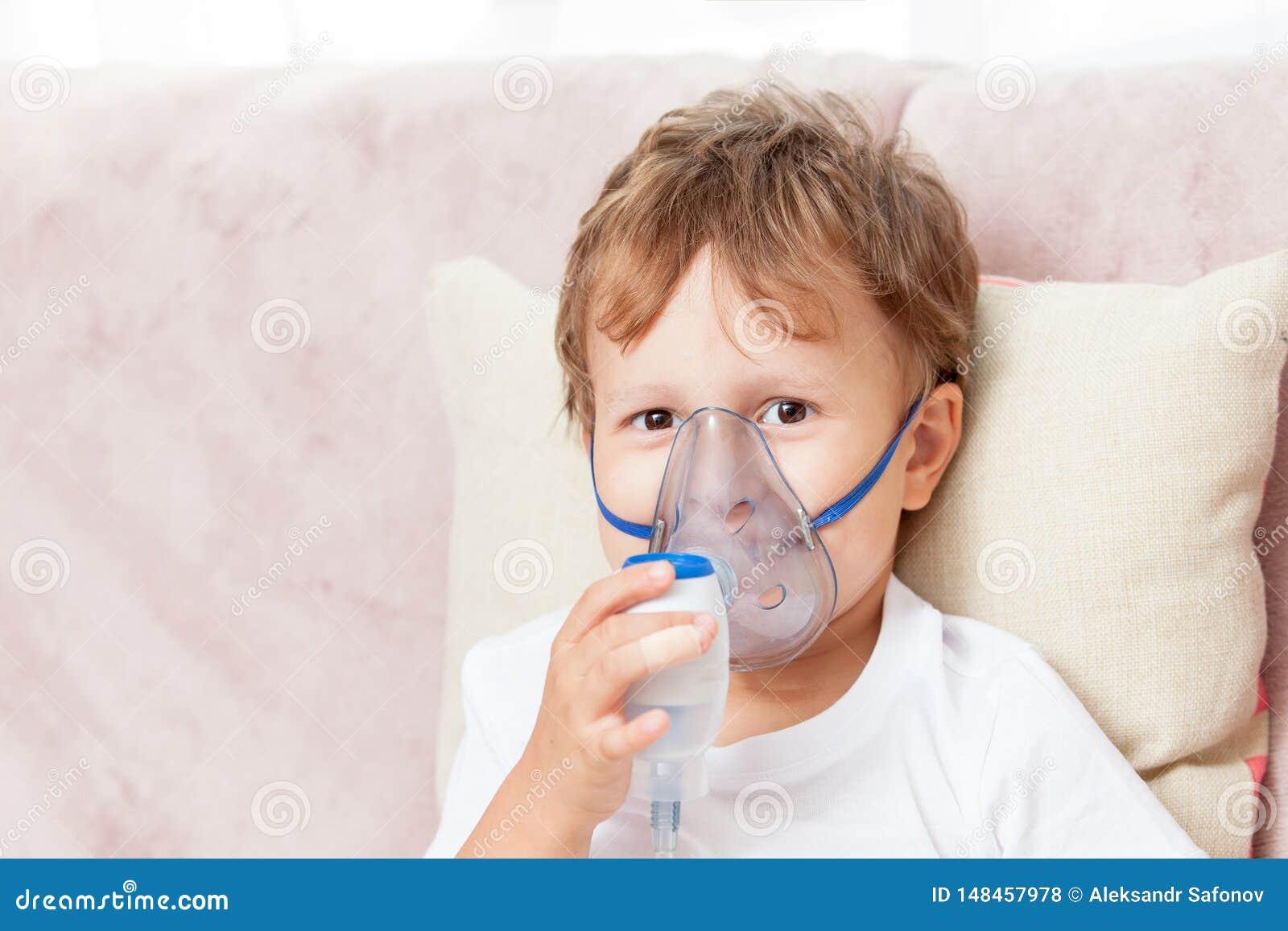 Menino que faz a inala??o com um nebulizer em casa