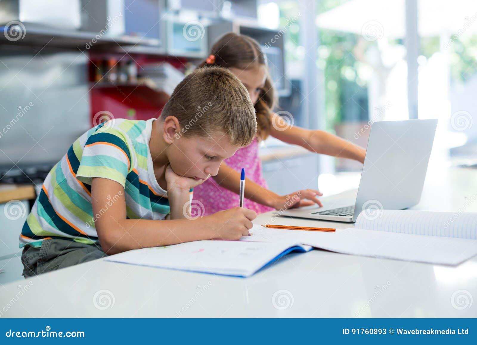 Menino que faz seus trabalhos de casa quando menina que usa o portátil na cozinha