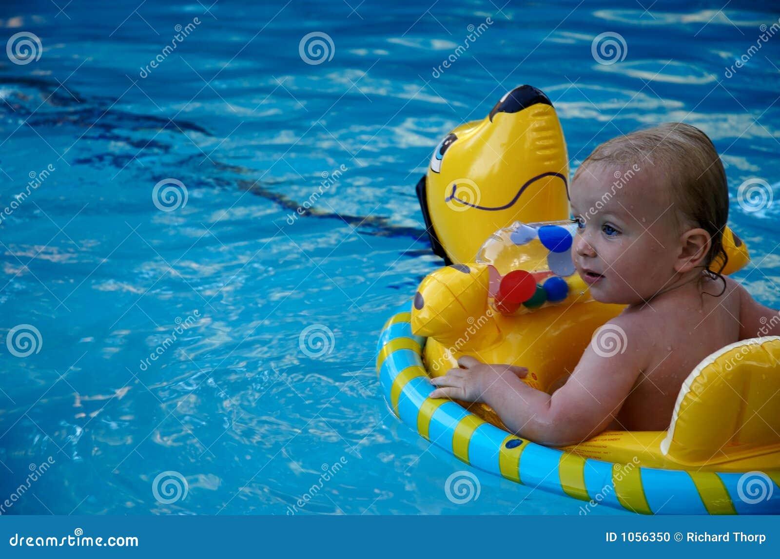 Menino que flutua em uma piscina