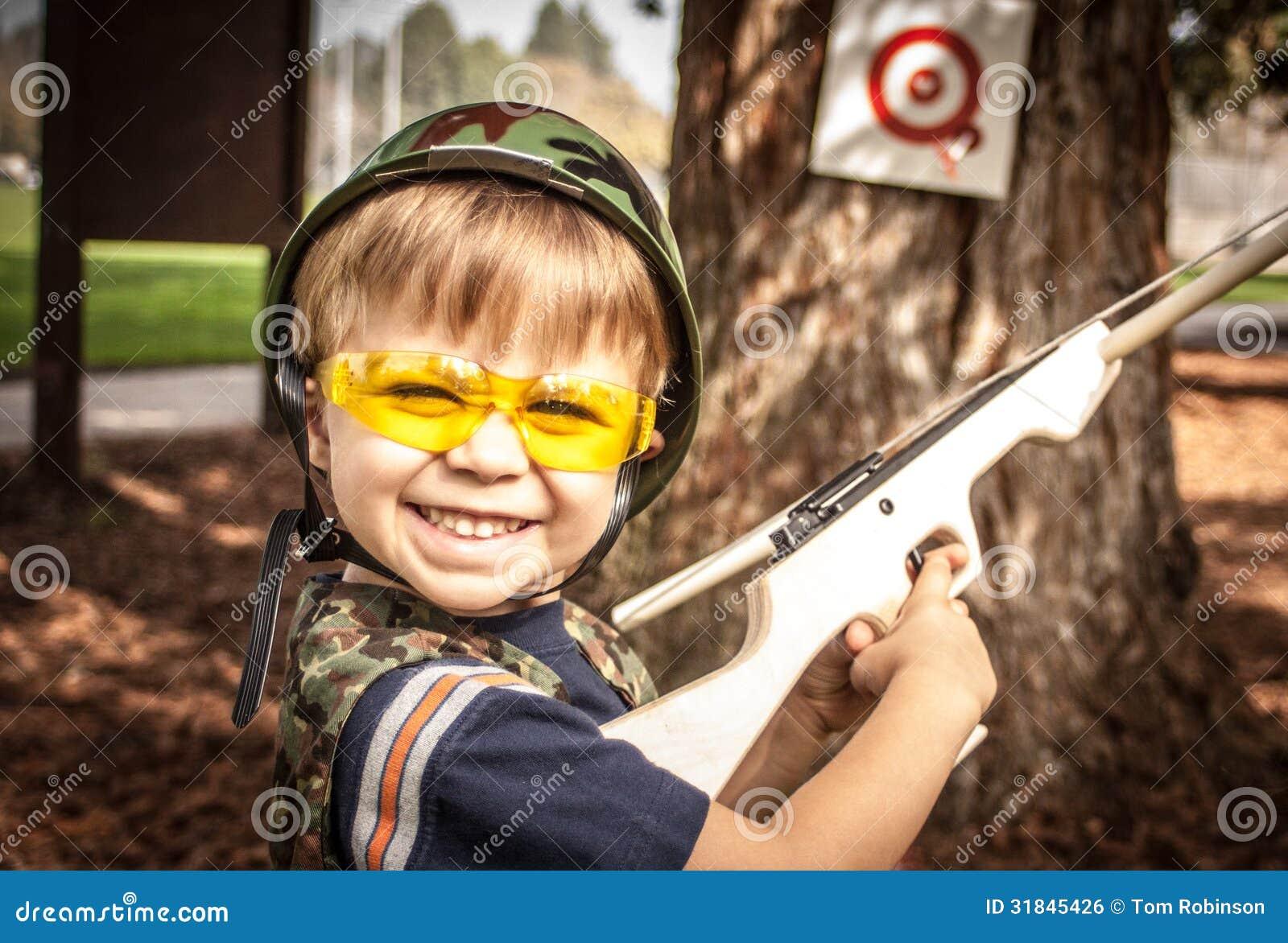 Arma Besta Wikipedia: Menino Que Joga Com A Arma Da Besta Do Brinquedo Imagem De