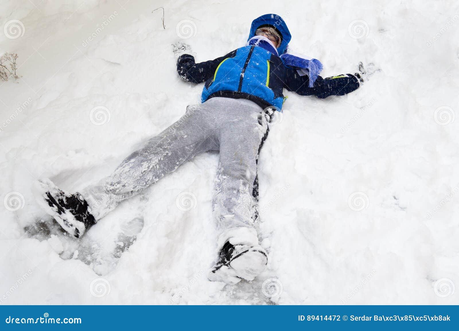 Menino que joga com neve