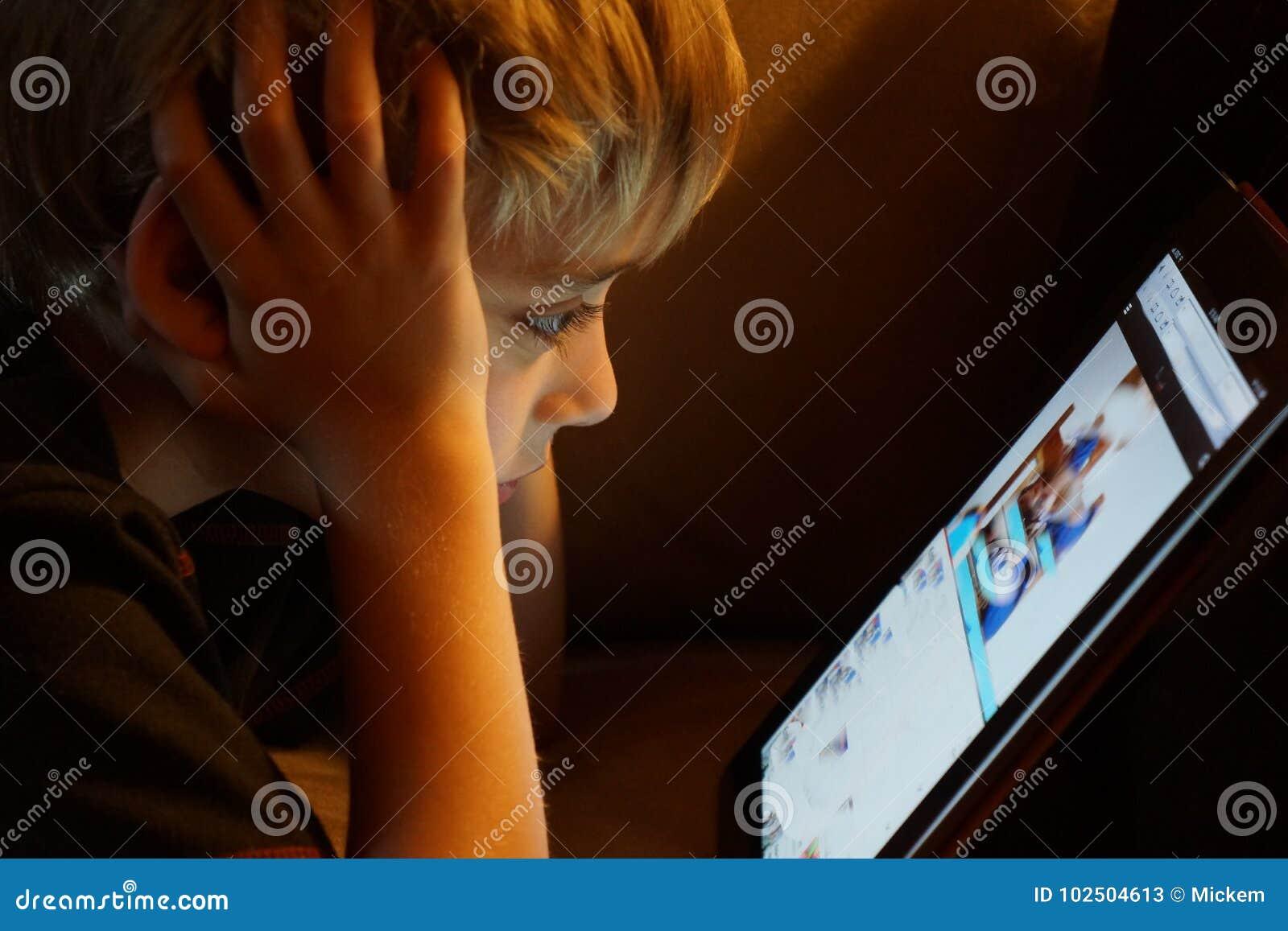 Menino que olha fixamente no tablet pc do iPad