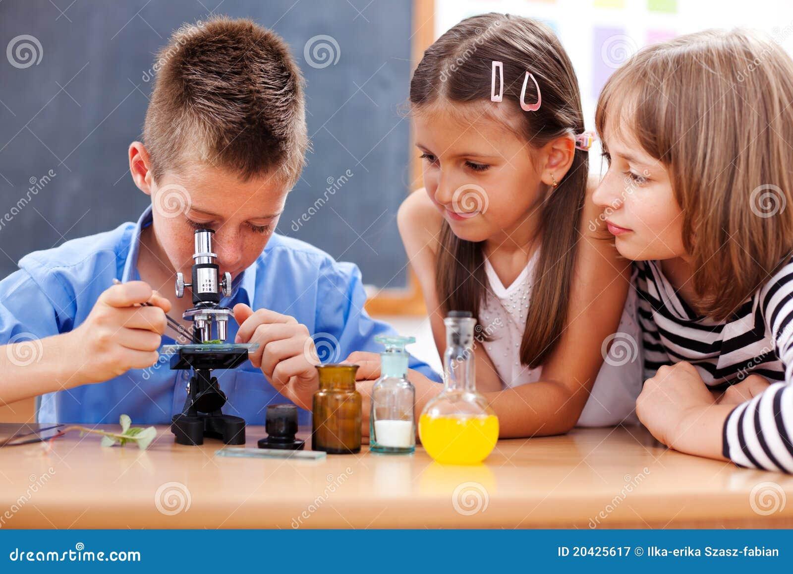 Menino que olha no microscópio