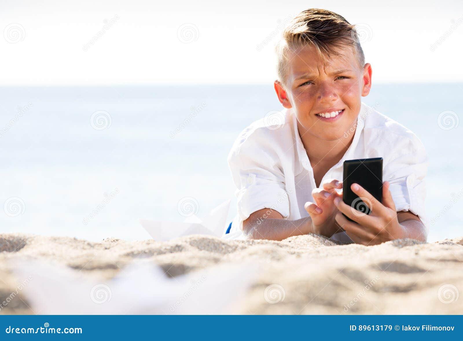 Menino que olha o telefone ao descansar na praia