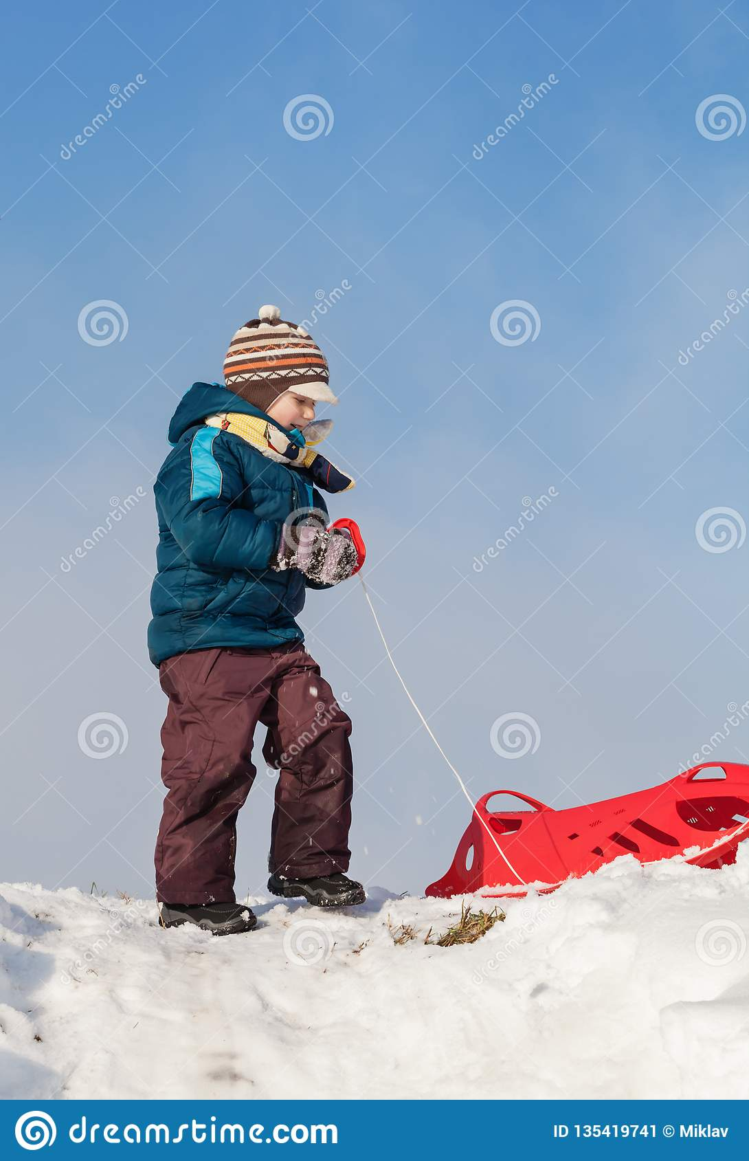 Menino que puxa o pequeno trenó plástico vermelho para um monte nevado