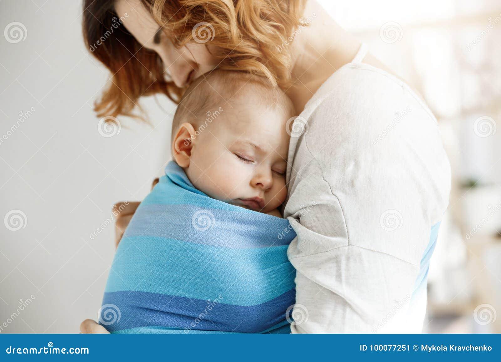 Menino recém-nascido muito pequeno que tem o sono profundo no dia na caixa da mãe no estilingue do bebê azul Mamã que beija a cab
