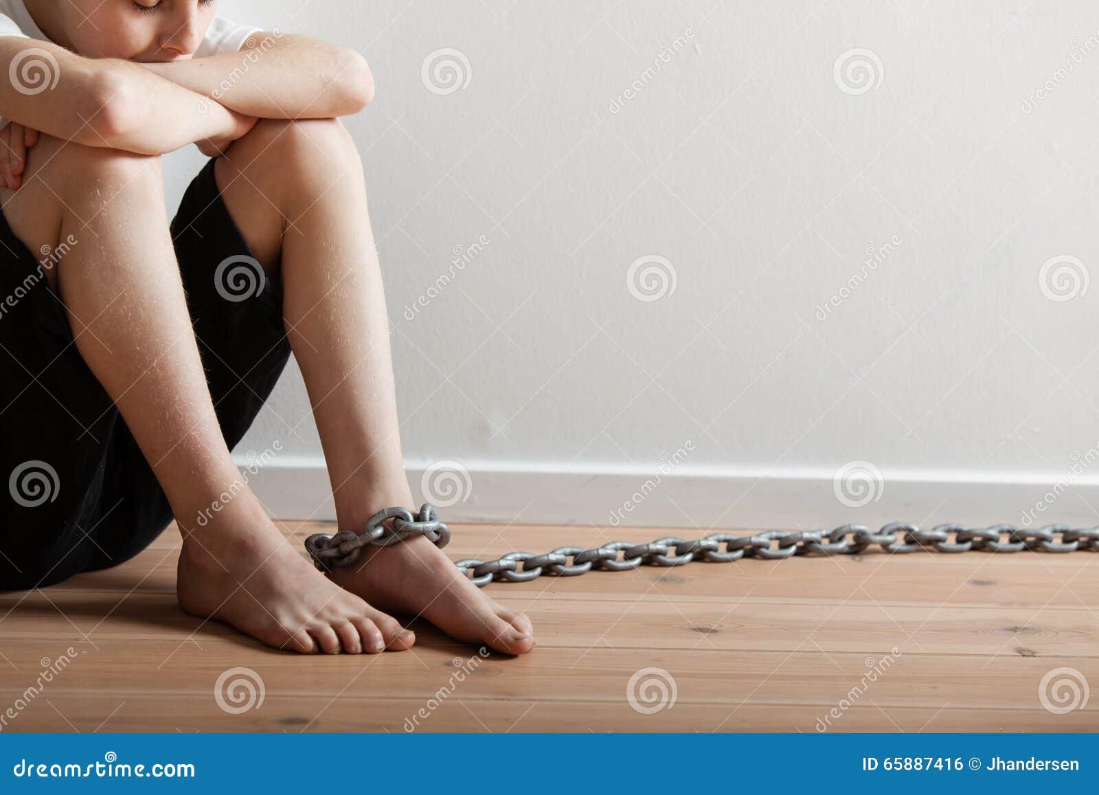 Menino só que senta-se em uma sala com corrente a pé
