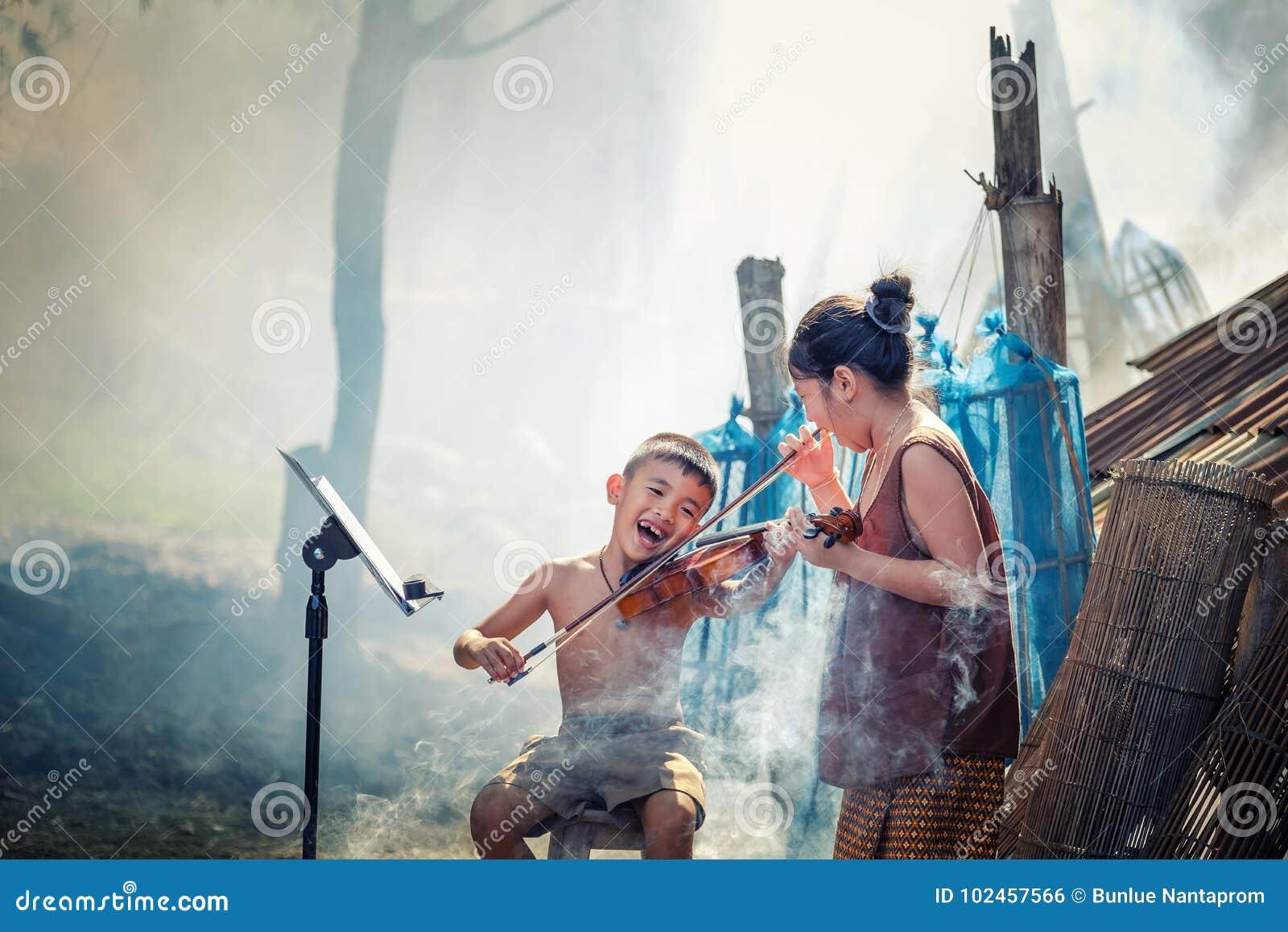 Menino tailandês e meninas rurais que jogam o violino em seu jardim home isto