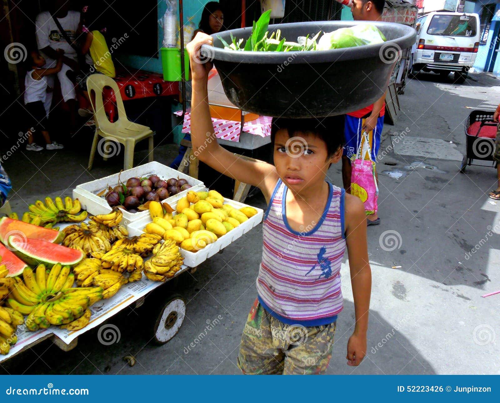 Meninos novos em um mercado do cainta, rizal, Filipinas que vendem frutas e legumes