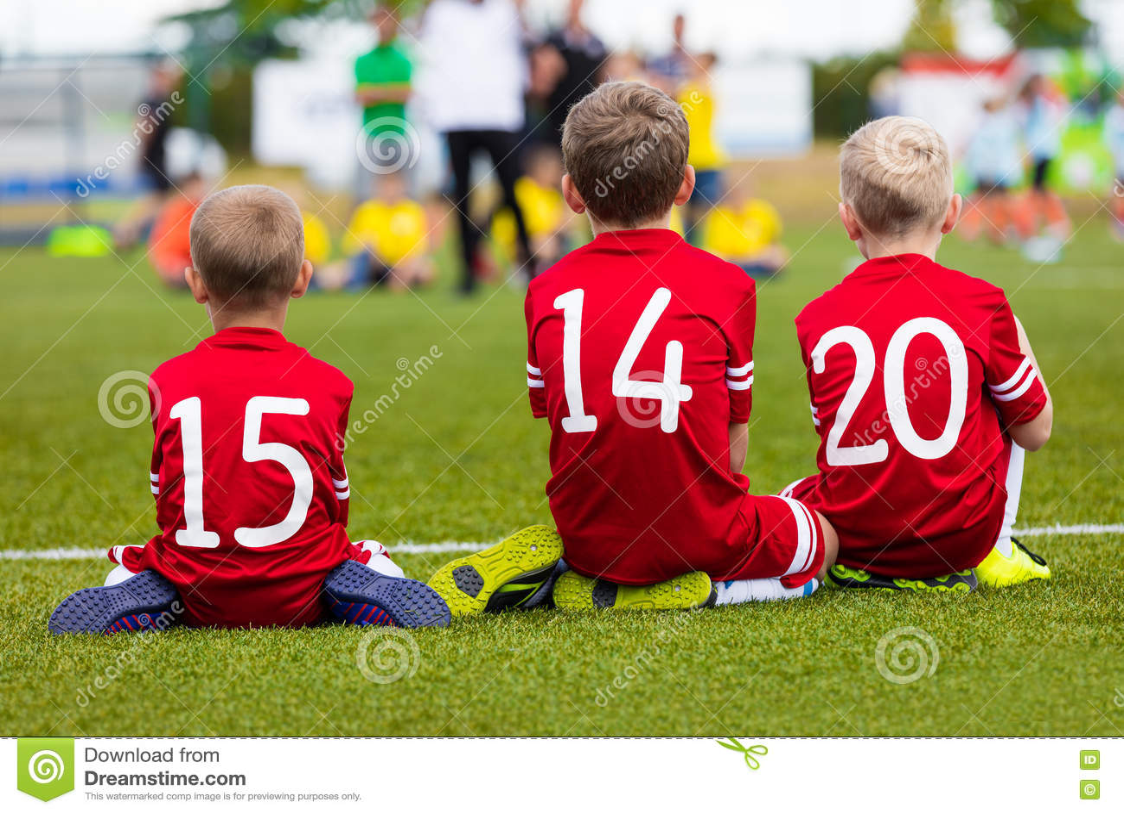 Meninos novos na equipe de futebol que senta-se junto no campo de esportes