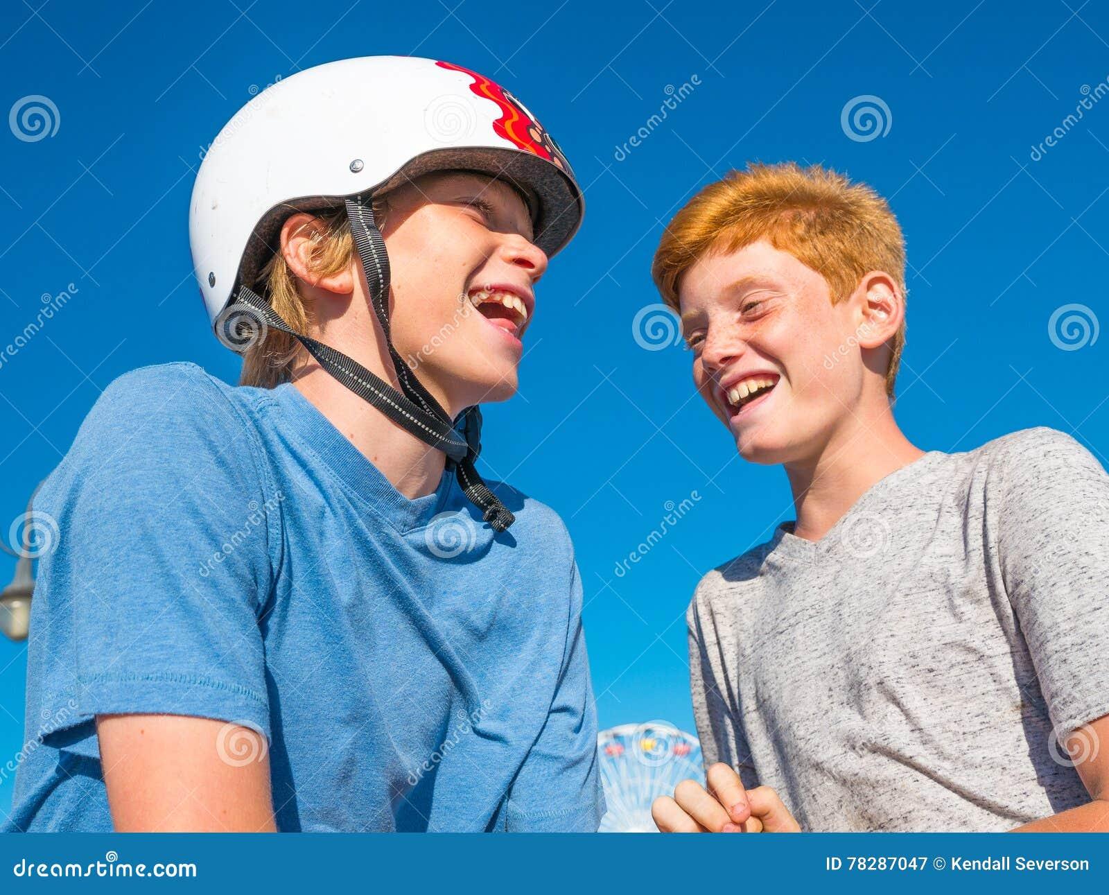 Meninos que jogam o papel, rocha, tesouras em Santa Monica Pier