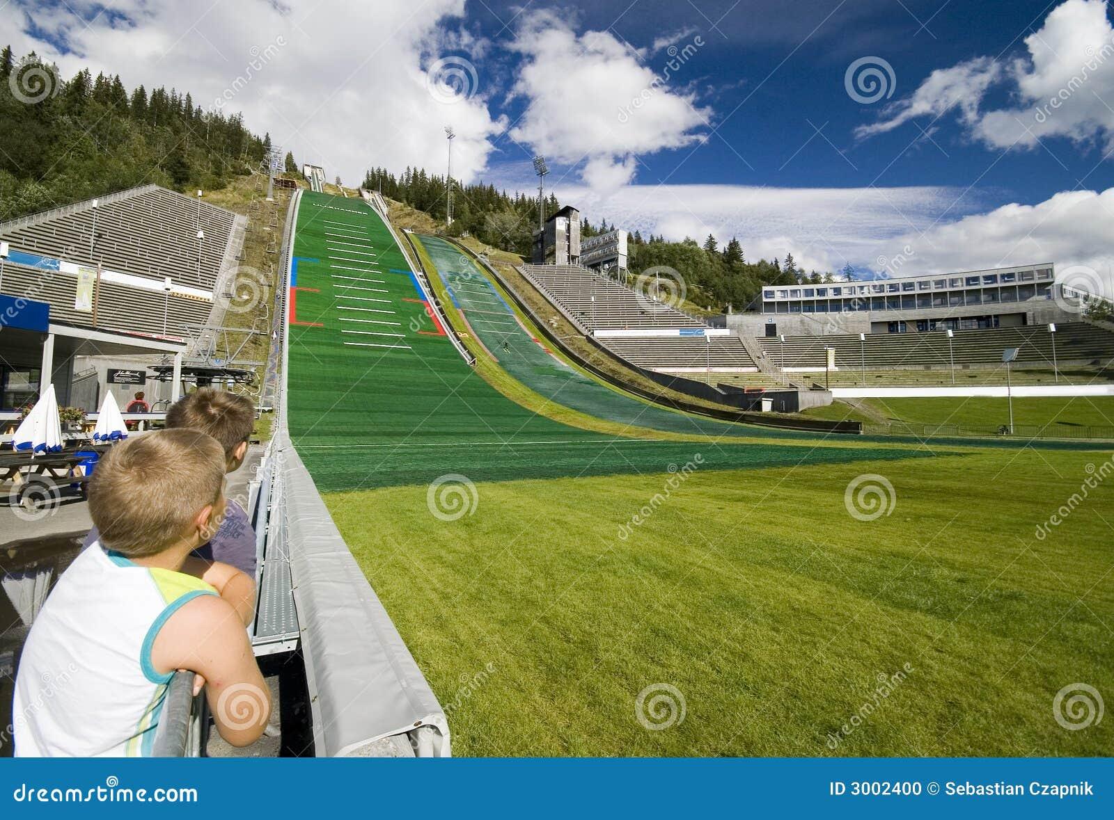 Meninos que prestam atenção a ligações em ponte de esqui.