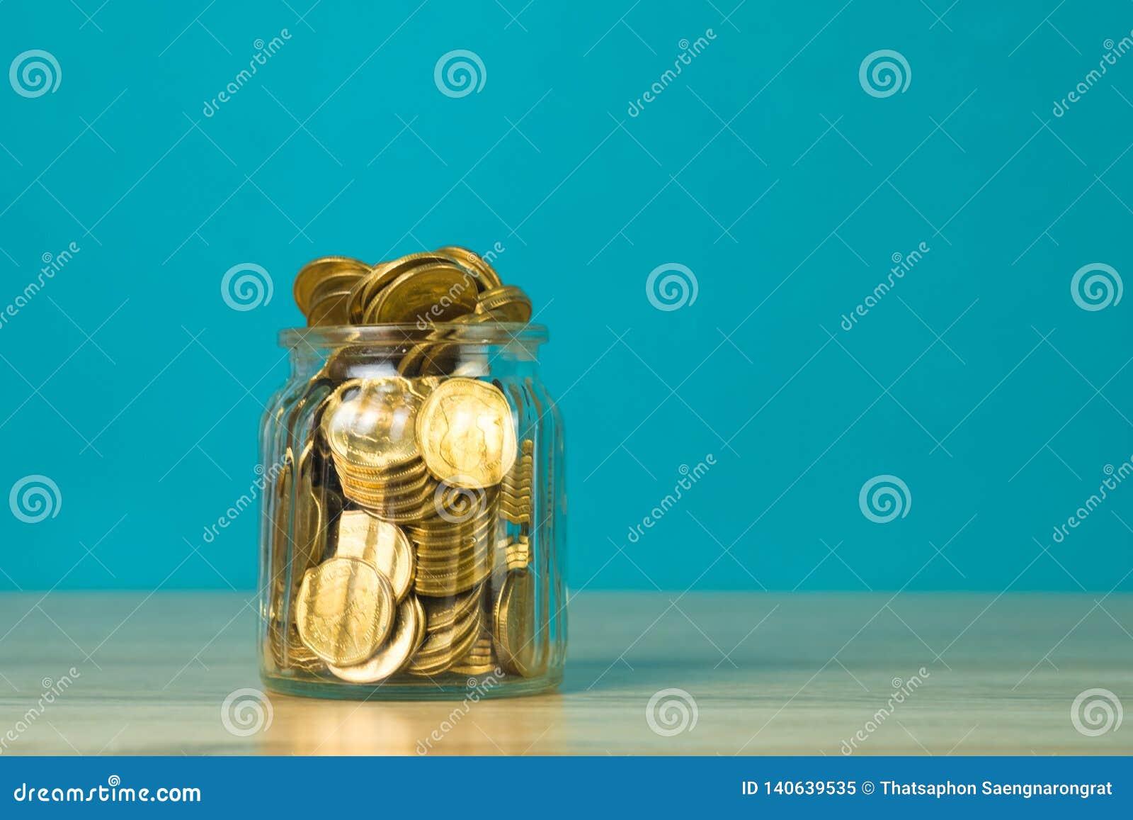Menniczy pieniądze w szklanym słoju na stole z zielonym tłem, ratować finansowego pojęcie dato che deponować pieniądze,