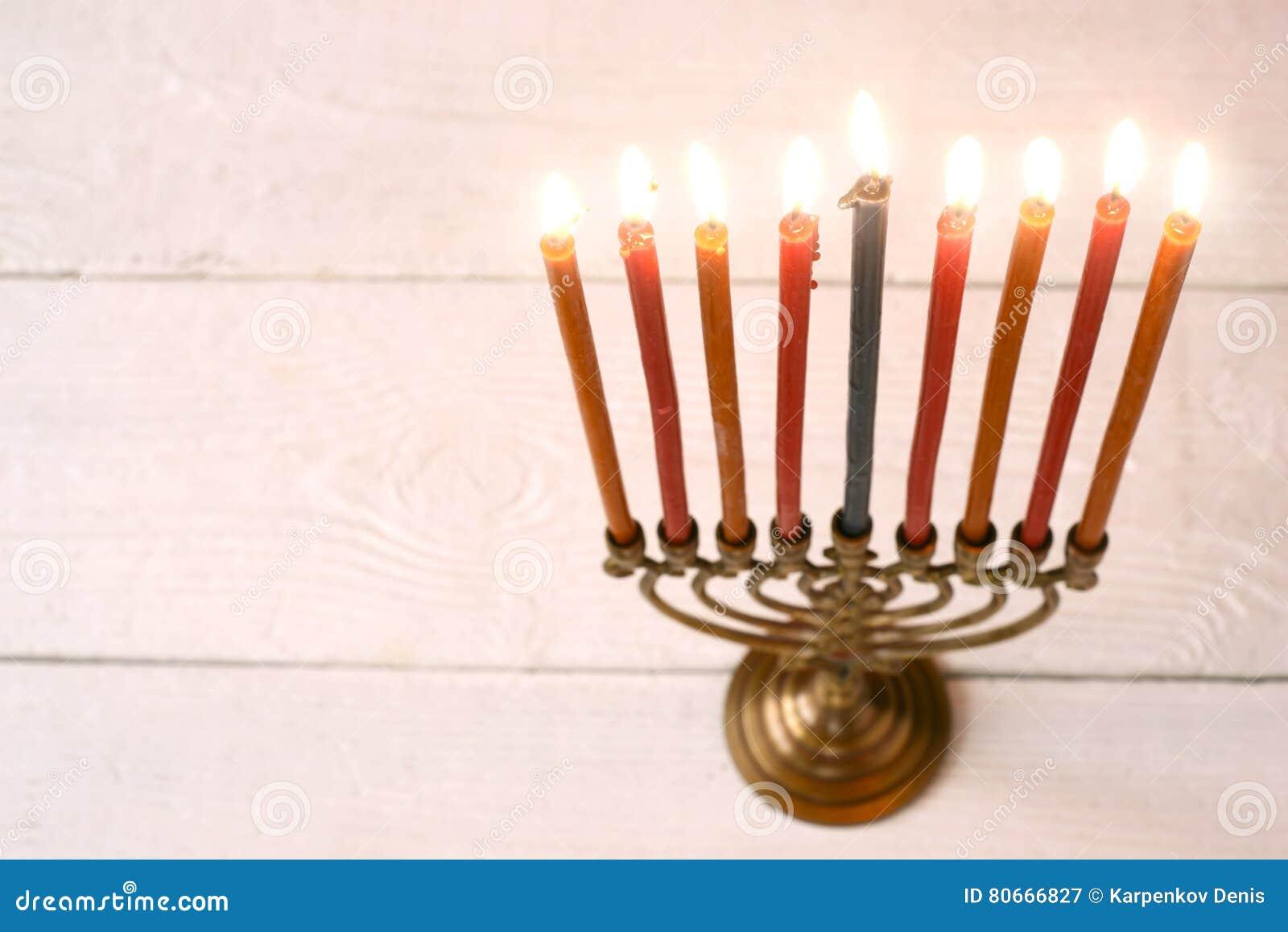 Menorah de Jánuca con las velas ardientes en la tabla de madera blanca horizontal