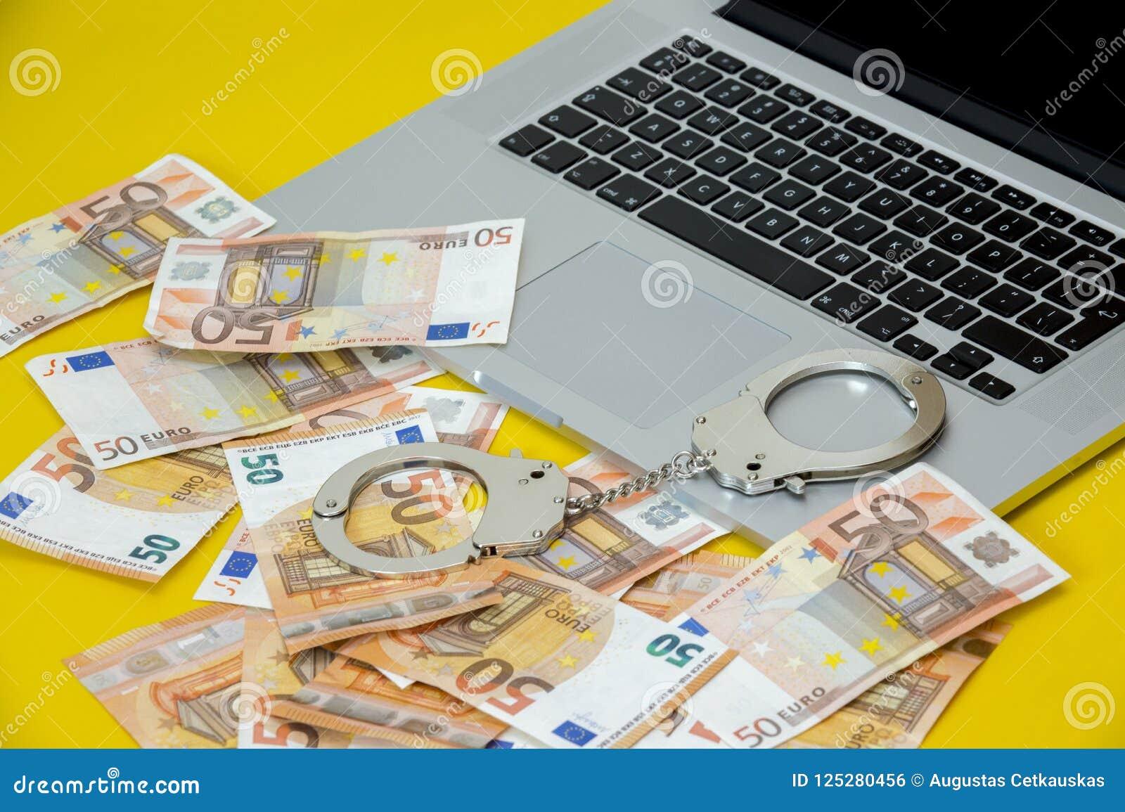 Menottes avec l argent sur le clavier d ordinateur portable