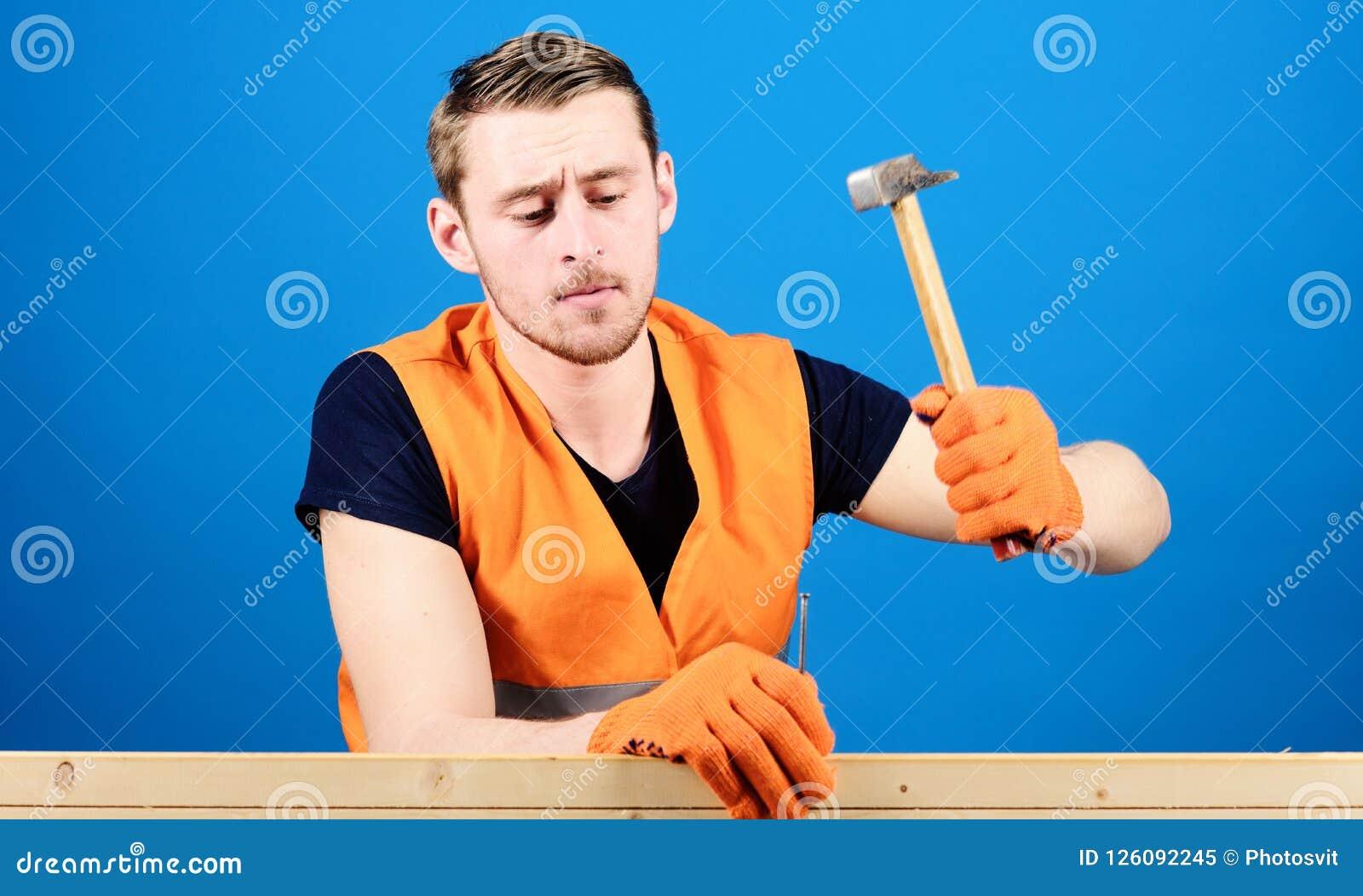 Mens, arbeider, manusje van alles in helder vest en beschermende handschoenen die, blauwe achtergrond handcrafting Handcraftingsc