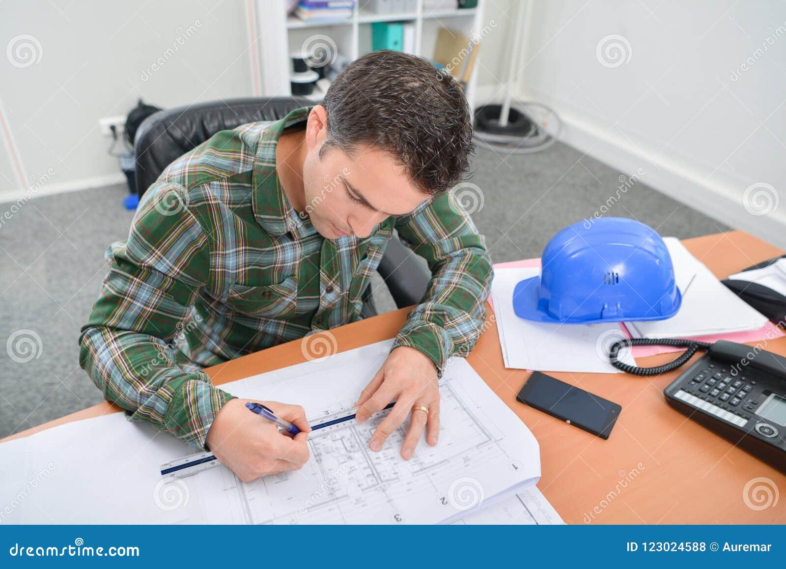 Mens bij bureau wordt gezeten die aan blauwdrukken werken die