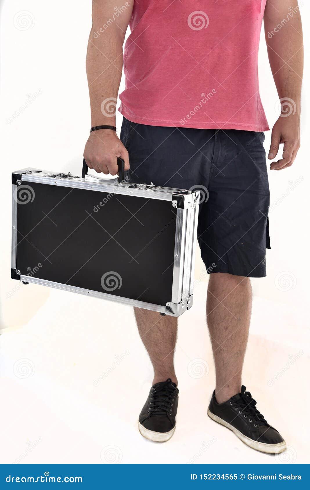 Mens in de Bermudas die zwarte aktentas op witte achtergrond dragen