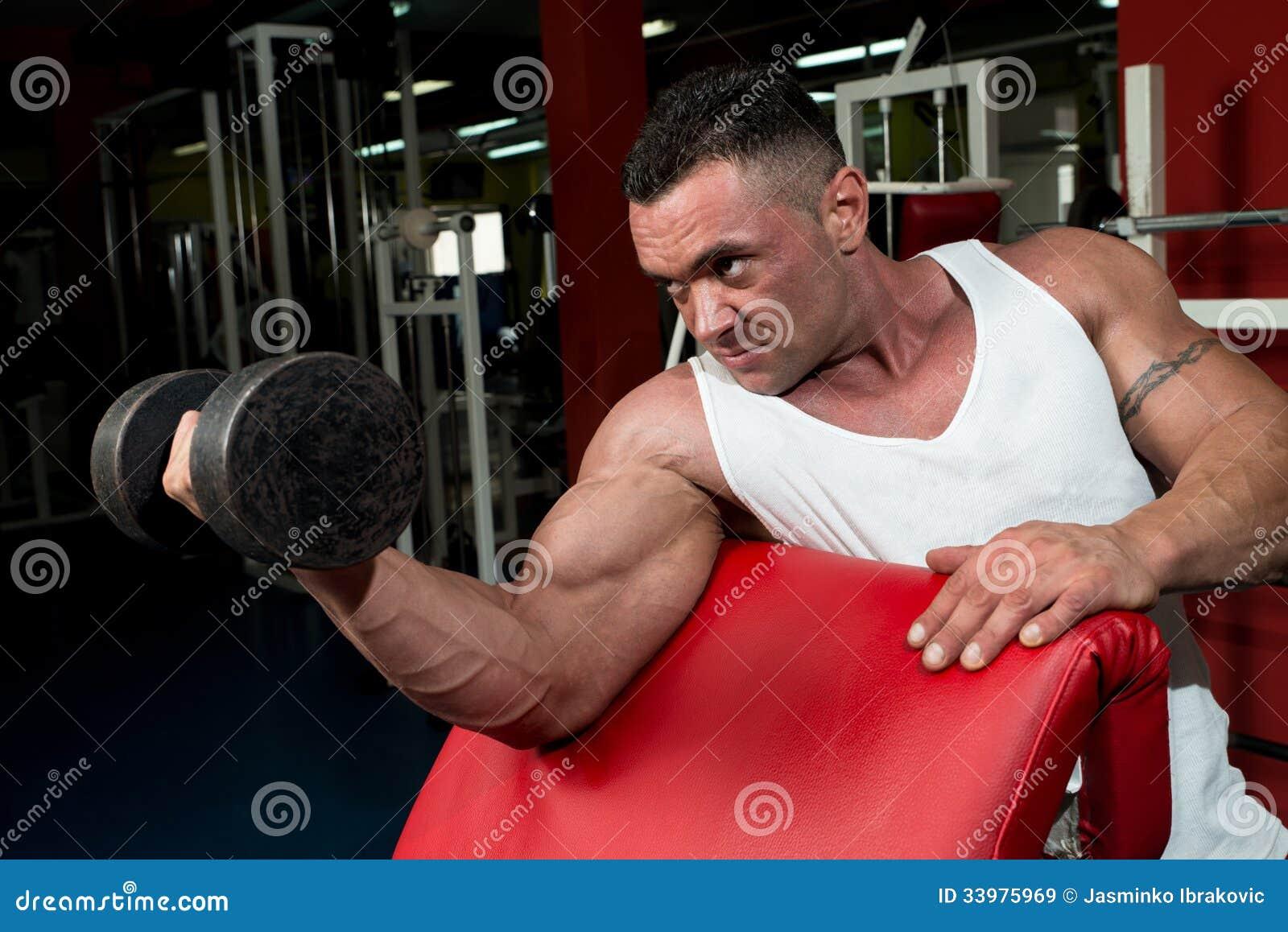 Mens in de Gymnastiek die Bicepsen met Domoren uitoefenen