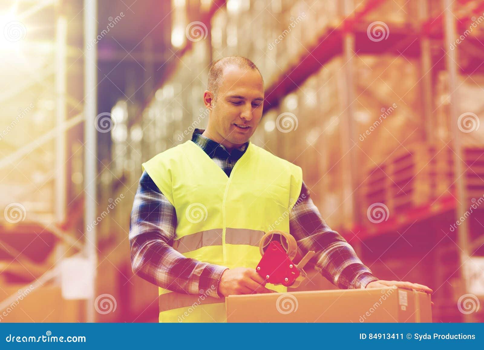 Mens in de verpakkingsdoos van het veiligheidsvest bij pakhuis