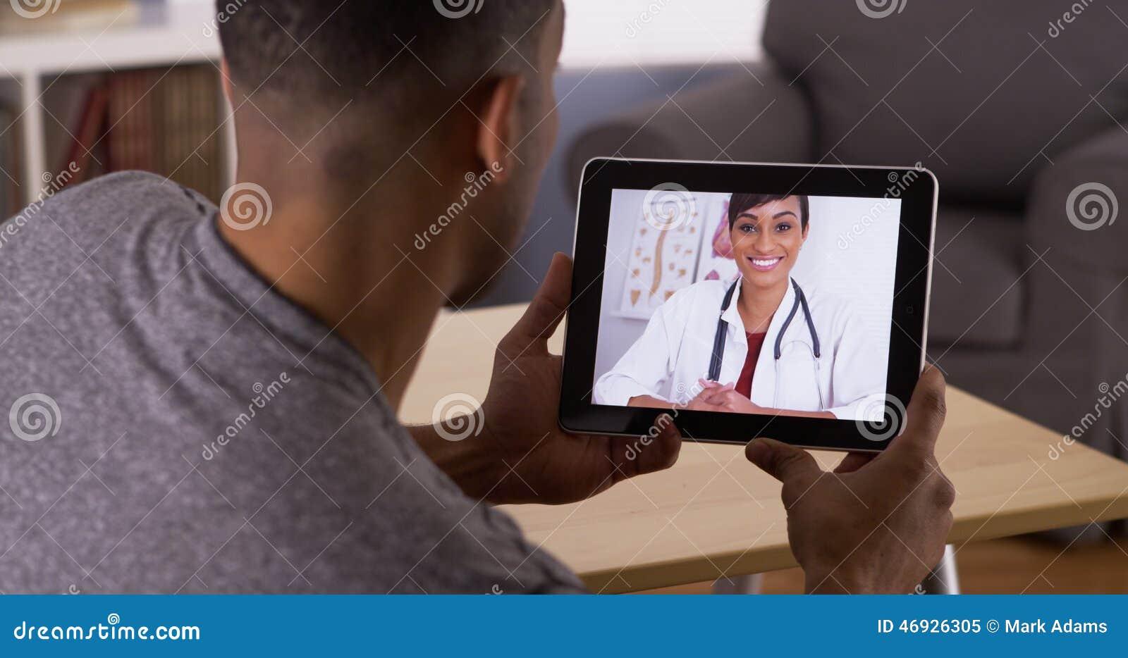 Mens die aan arts op tablet luisteren
