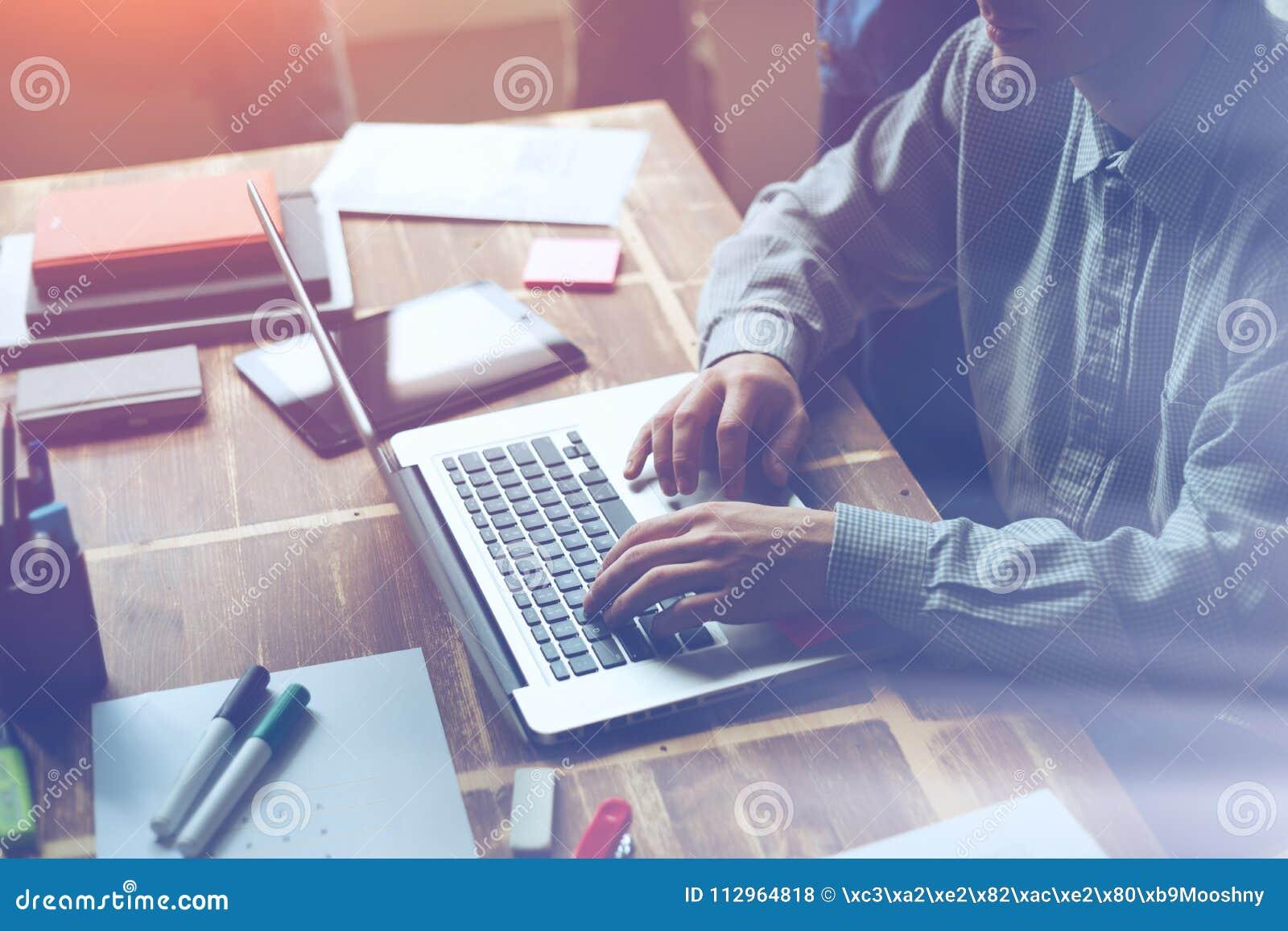 Mens die aan een project in open plekbureau werken Administratie en laptop op de lijst
