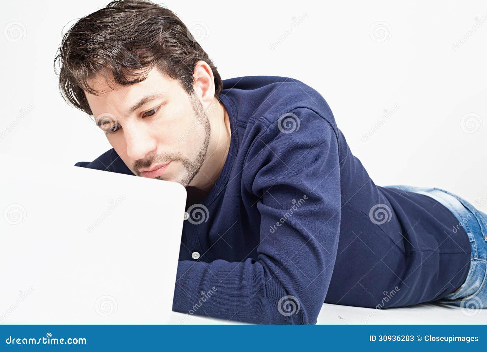 Mens die aan laptop werken terwijl het leggen op de vloer